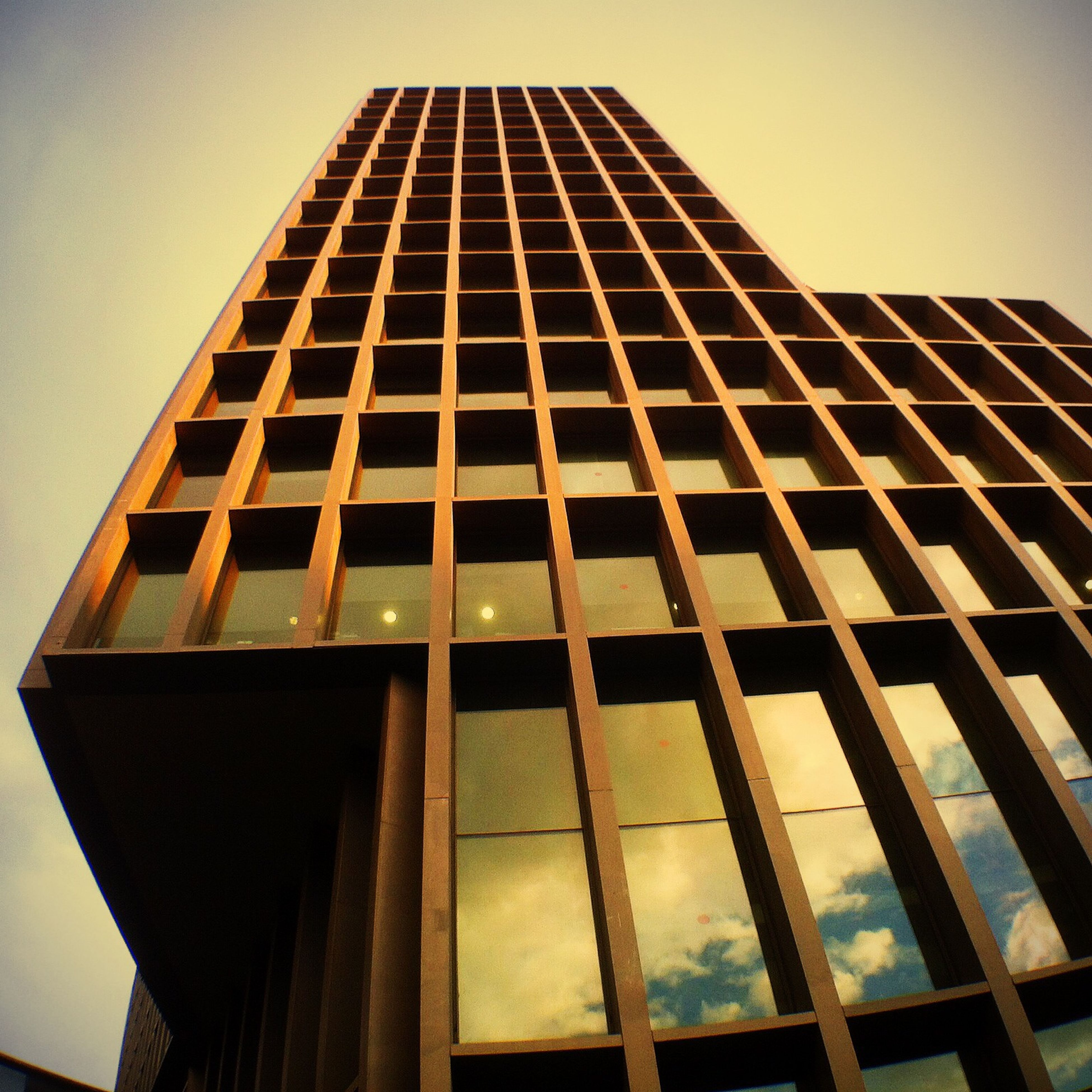 architecture, built structure, building exterior, low angle view, modern, glass - material, window, building, office building, reflection, sky, city, tall - high, pattern, geometric shape, clear sky, tower, skyscraper, no people, day