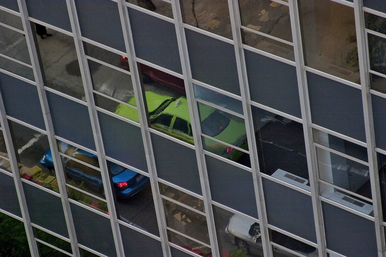 Cars Reflecting On Glass Windows Of Building