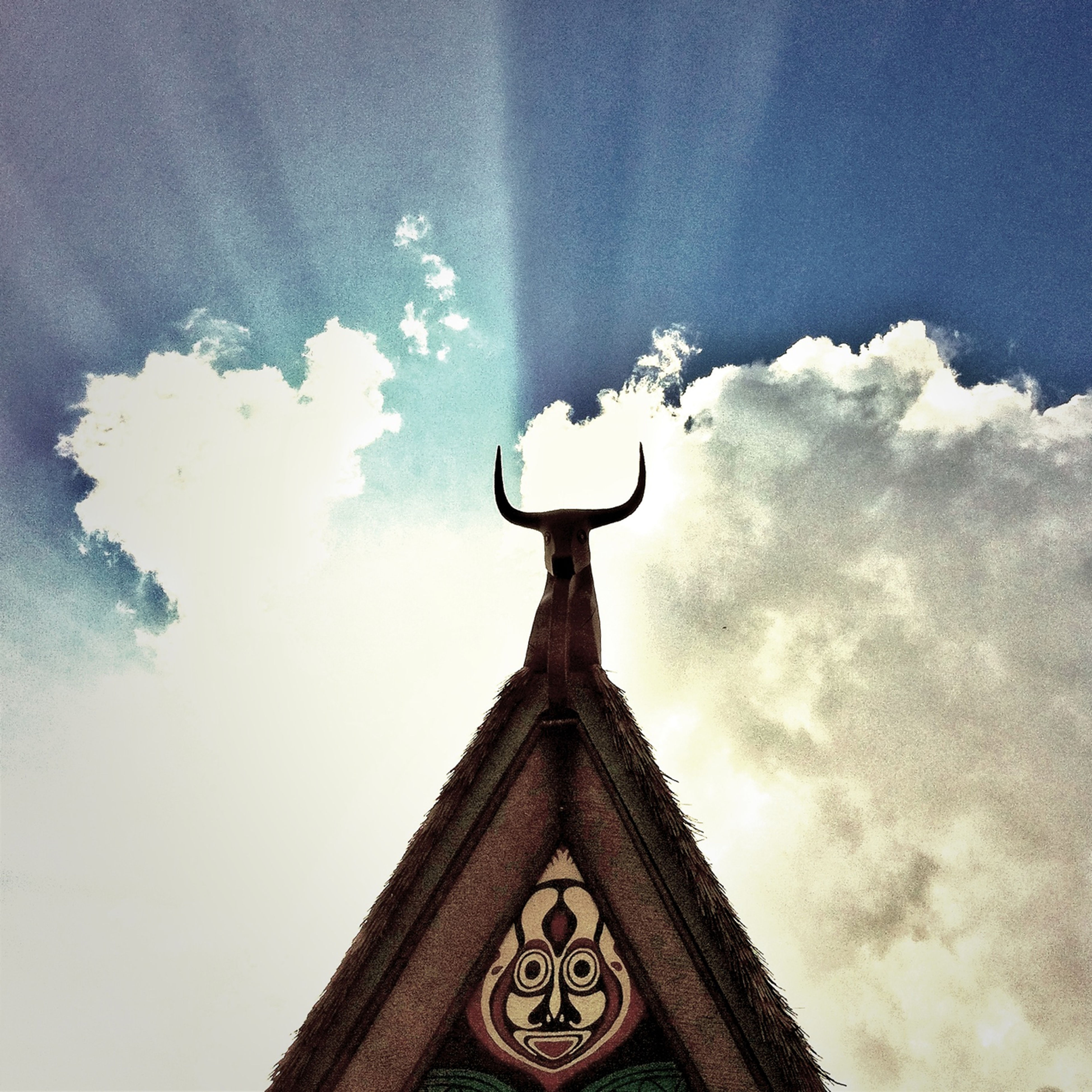 low angle view, sky, architecture, building exterior, religion, built structure, spirituality, high section, place of worship, cross, cloud - sky, church, text, human representation, communication, outdoors, no people, cloud