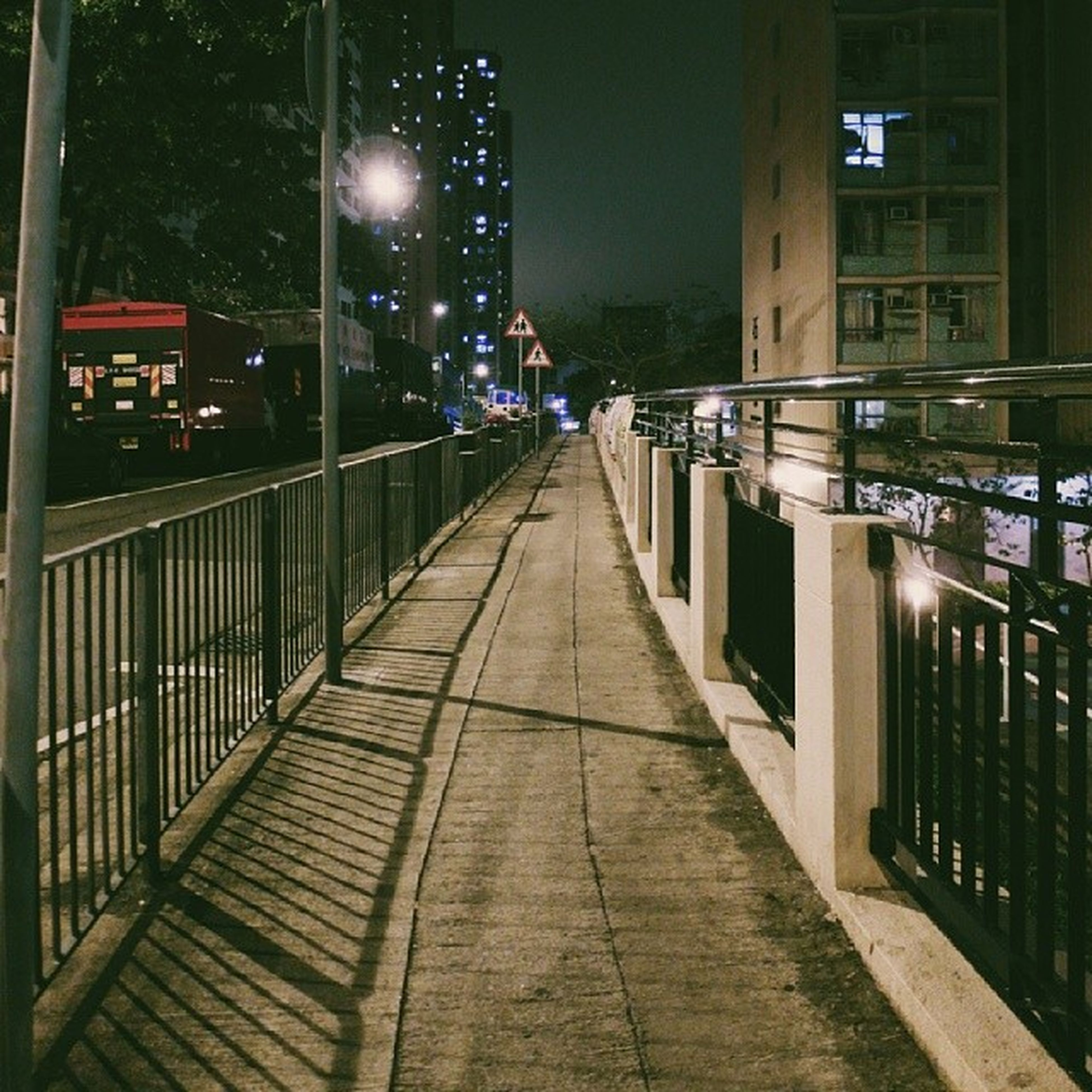 architecture, building exterior, built structure, the way forward, illuminated, night, city, street light, diminishing perspective, lighting equipment, building, street, residential building, vanishing point, residential structure, railing, outdoors, sidewalk, empty, narrow