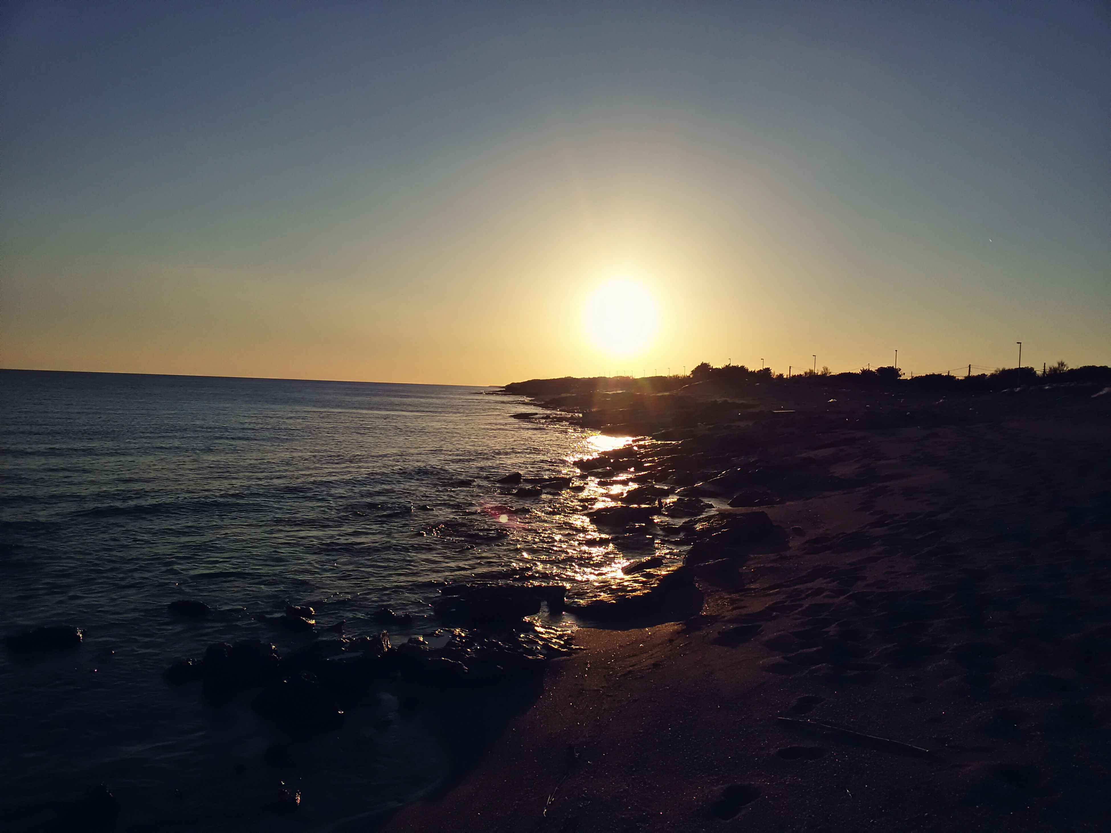 sea, water, sunset, beach, clear sky, horizon over water, scenics, sun, shore, beauty in nature, tranquil scene, copy space, tranquility, nature, silhouette, idyllic, sunlight, wave, sky, incidental people