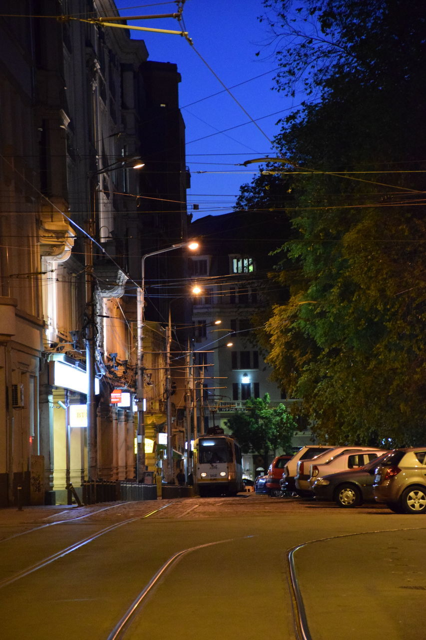 architecture, street, building exterior, built structure, transportation, illuminated, night, road, car, city, cable, street light, outdoors, electricity, tree, no people, sky