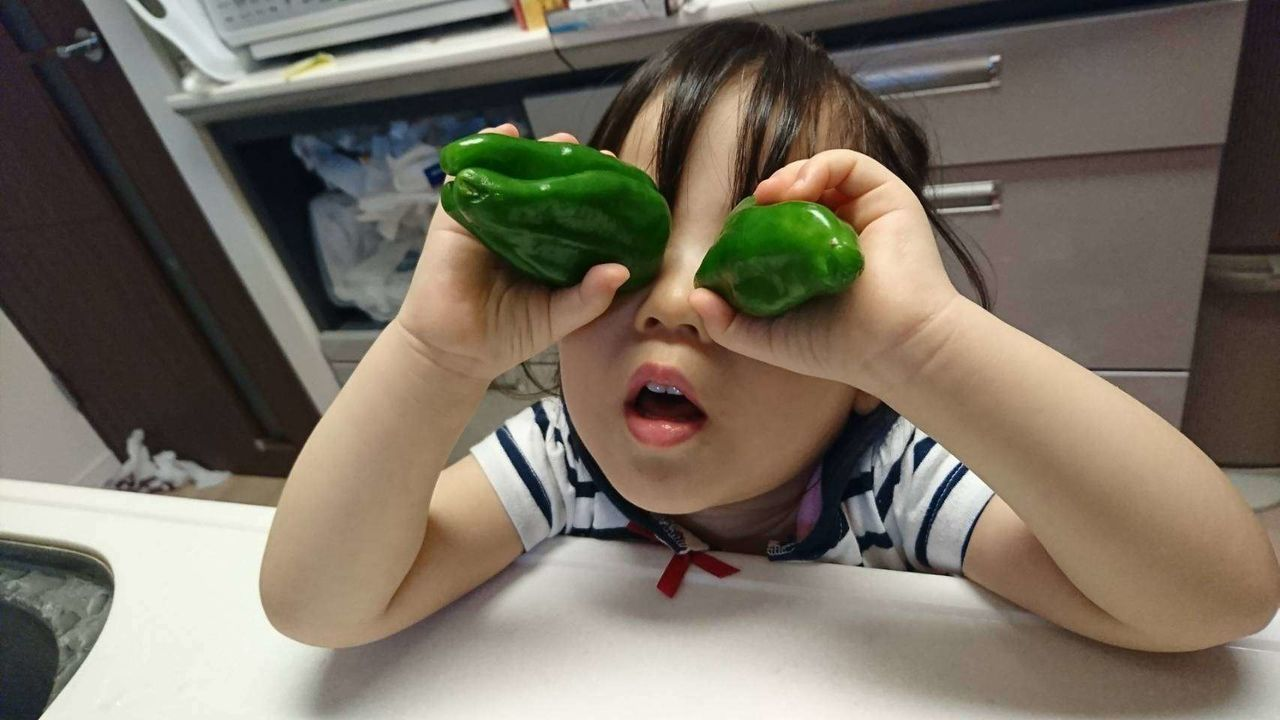 High Angle View Of Baby Girl Covering Eyes With Bell Peppers In Kitchen