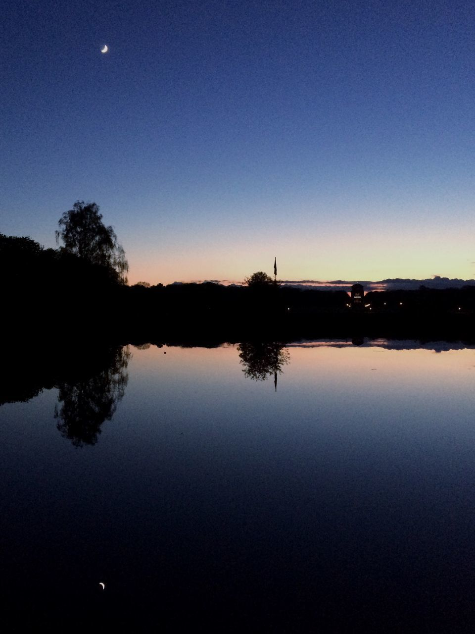 reflection, silhouette, water, tranquil scene, tranquility, nature, no people, lake, outdoors, scenics, sky, clear sky, beauty in nature, dusk, sunset, tree, blue, moon, day