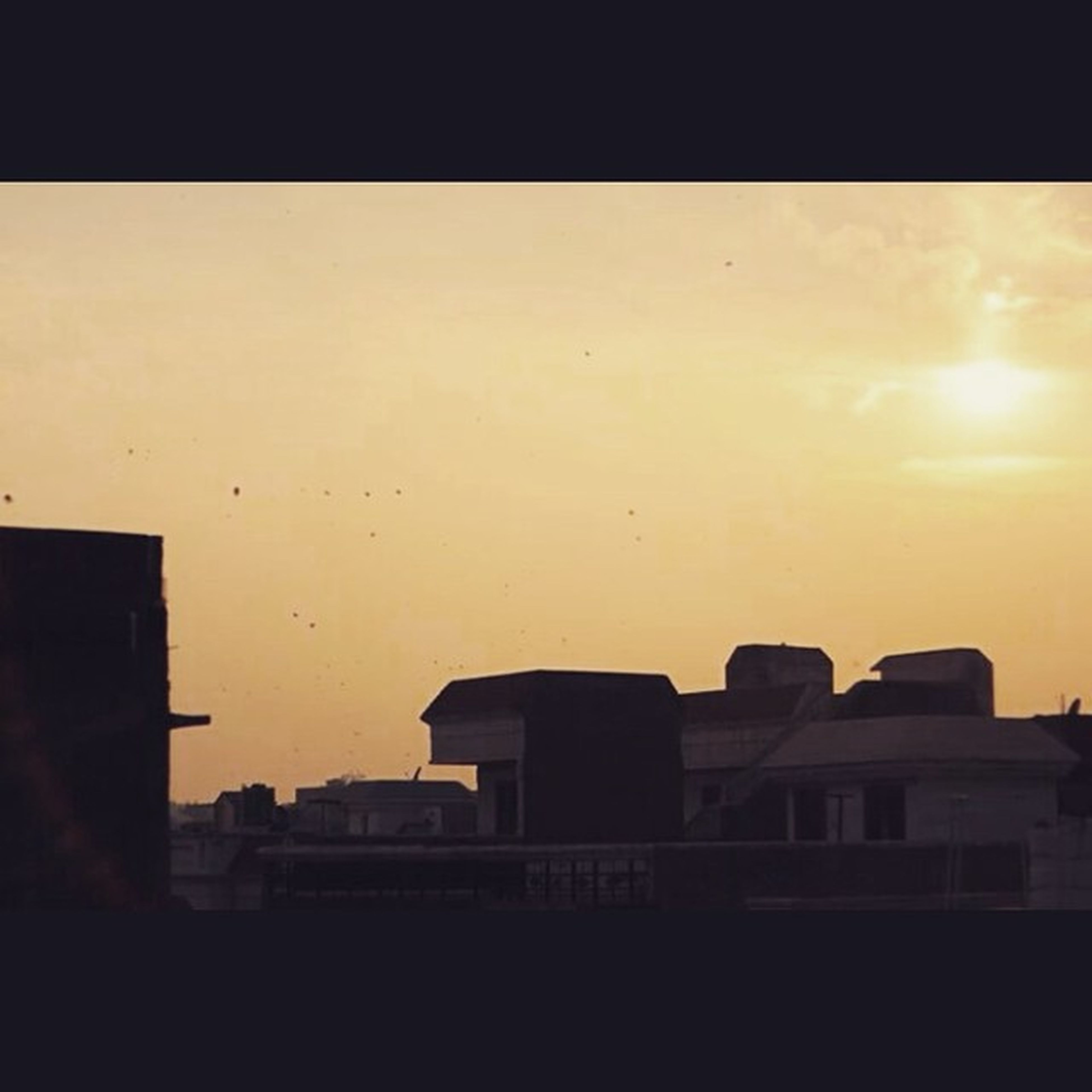 building exterior, architecture, built structure, sunset, transfer print, silhouette, auto post production filter, sky, residential structure, building, window, house, residential building, city, dusk, outdoors, low angle view, no people, dark, sunlight
