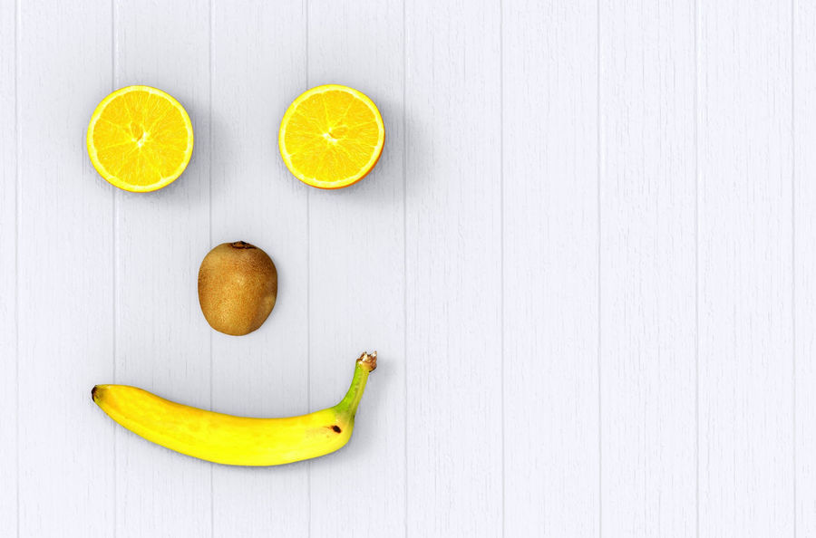 lemon as eyes, kiwee as nose and banana as mouth on gray wood table background. Love Fruits concept Shape Wood Aerial View Banana Citrus Fruit Close-up Directly Above Food Freshness Fruit Health Healthy Eating Lemon Love Fruits SLICE Smile Studio Shot Table White Background Yellow