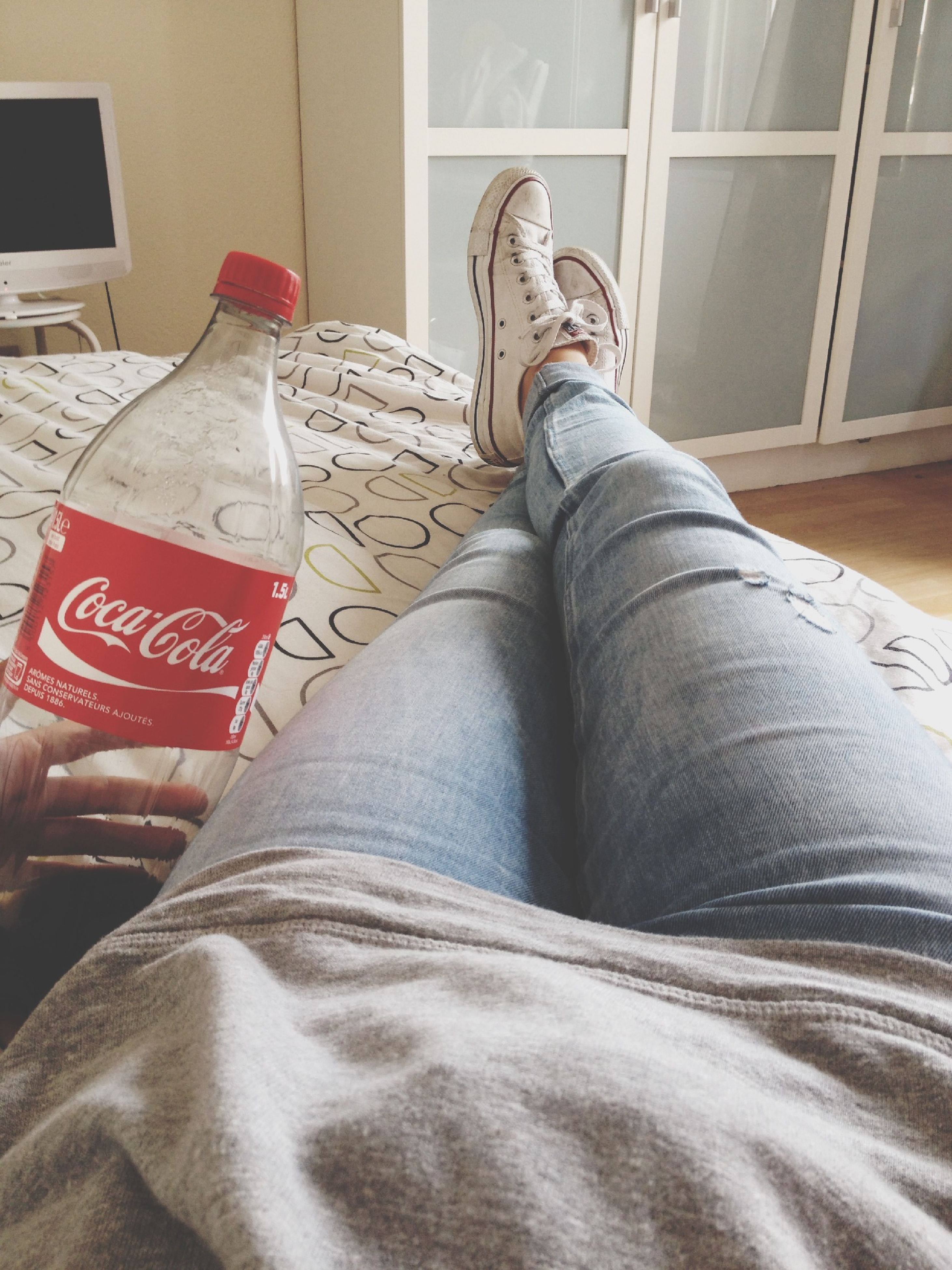 person, low section, indoors, relaxation, personal perspective, shoe, lifestyles, jeans, bed, human foot, legs crossed at ankle, resting, sitting, home interior, casual clothing, lying down, leisure activity