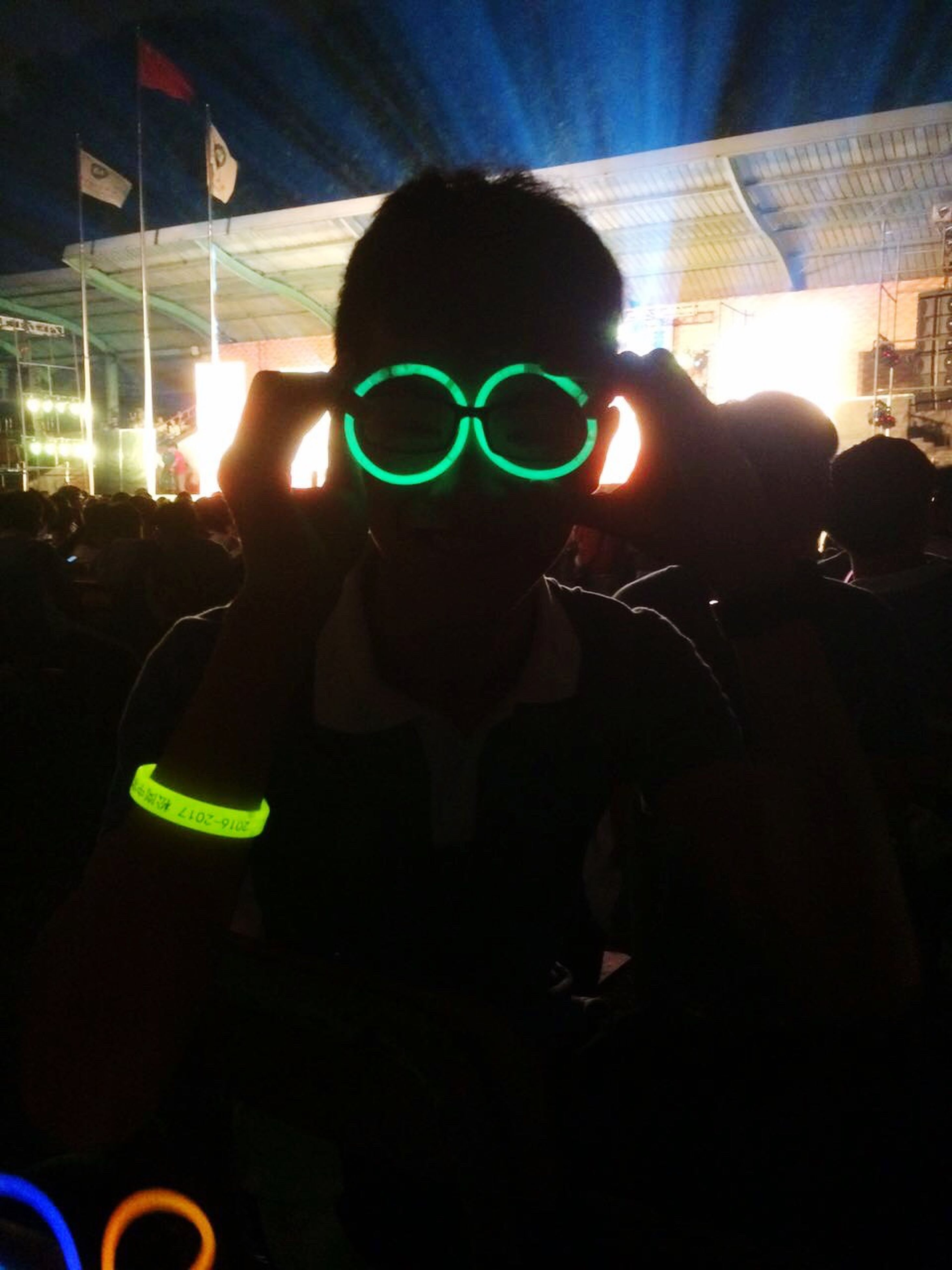 illuminated, indoors, leisure activity, lifestyles, night, arts culture and entertainment, men, light - natural phenomenon, music, fun, person, multi colored, enjoyment, holding, nightclub, unrecognizable person, technology