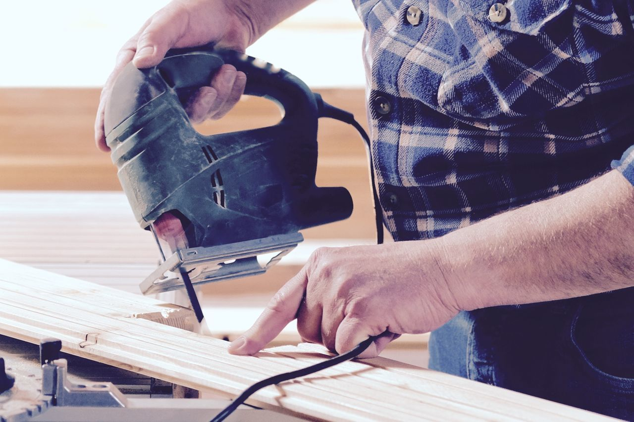 Midsection Of Man Using Power Tool On Wood At Home