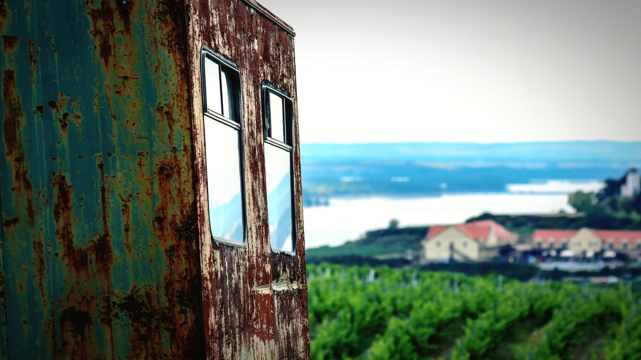 weathered, run-down, obsolete, damaged, no people, abandoned, rusty, window, bad condition, day, green color, built structure, focus on foreground, close-up, outdoors, architecture, sky, building exterior, tree, nature
