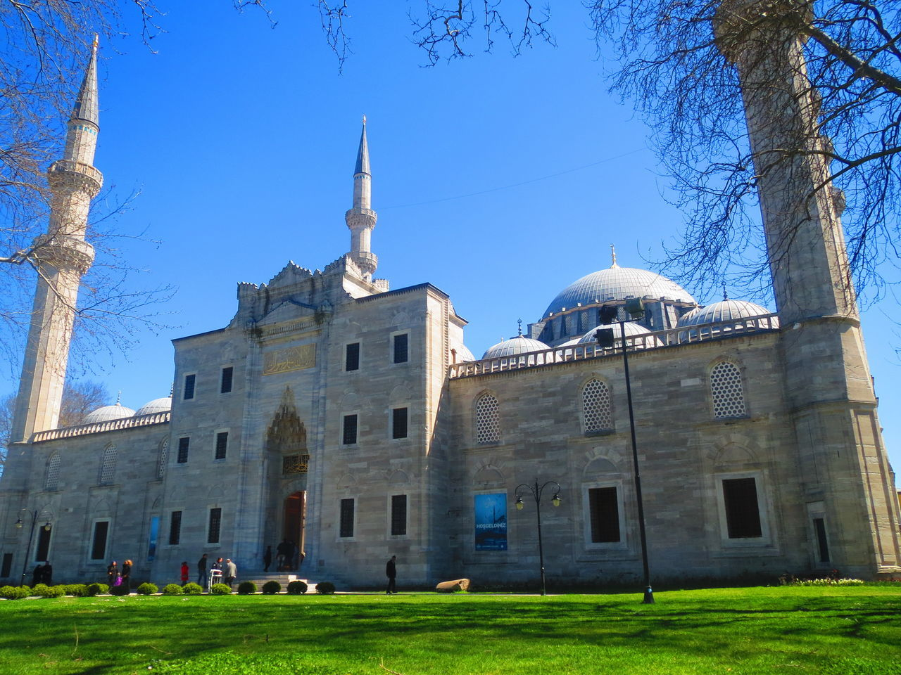 architecture, building exterior, built structure, religion, place of worship, spirituality, day, low angle view, blue, outdoors, dome, travel destinations, clear sky, history, sunlight, bare tree, tree, grass, sky, no people, city