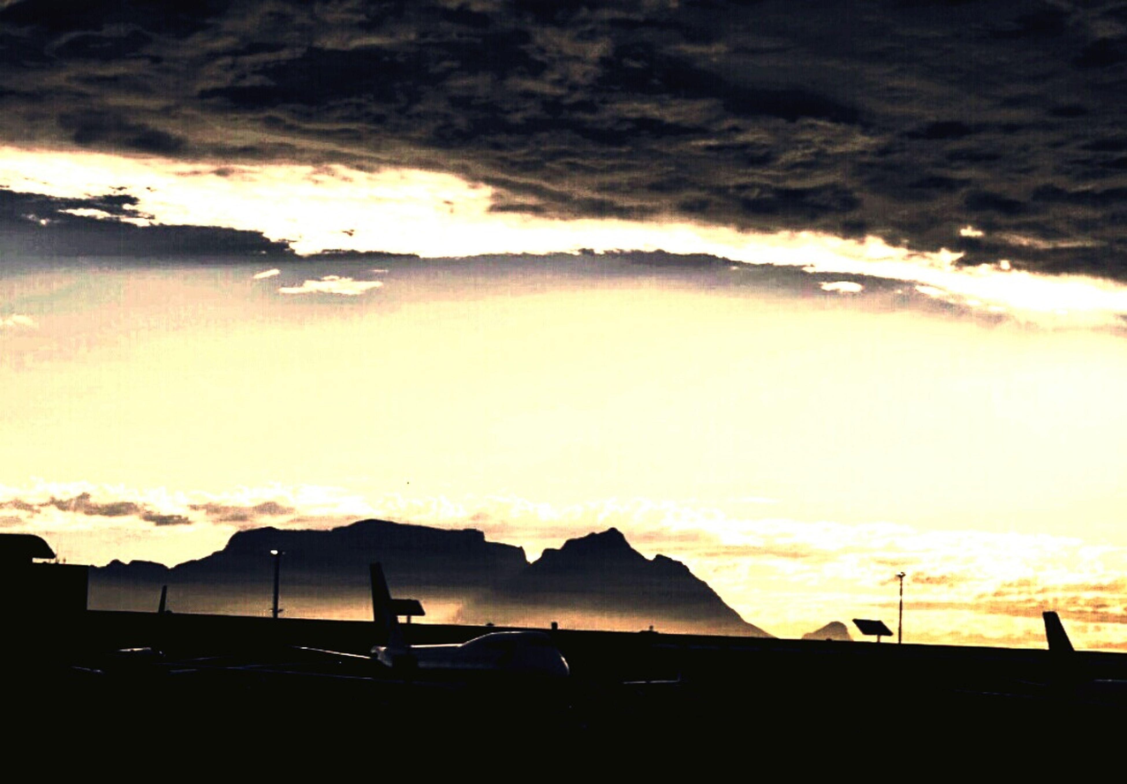 sunset, sky, cloud - sky, silhouette, scenics, cloudy, beauty in nature, mountain, dramatic sky, weather, orange color, cloud, tranquil scene, dusk, nature, tranquility, transportation, idyllic, sea, mode of transport