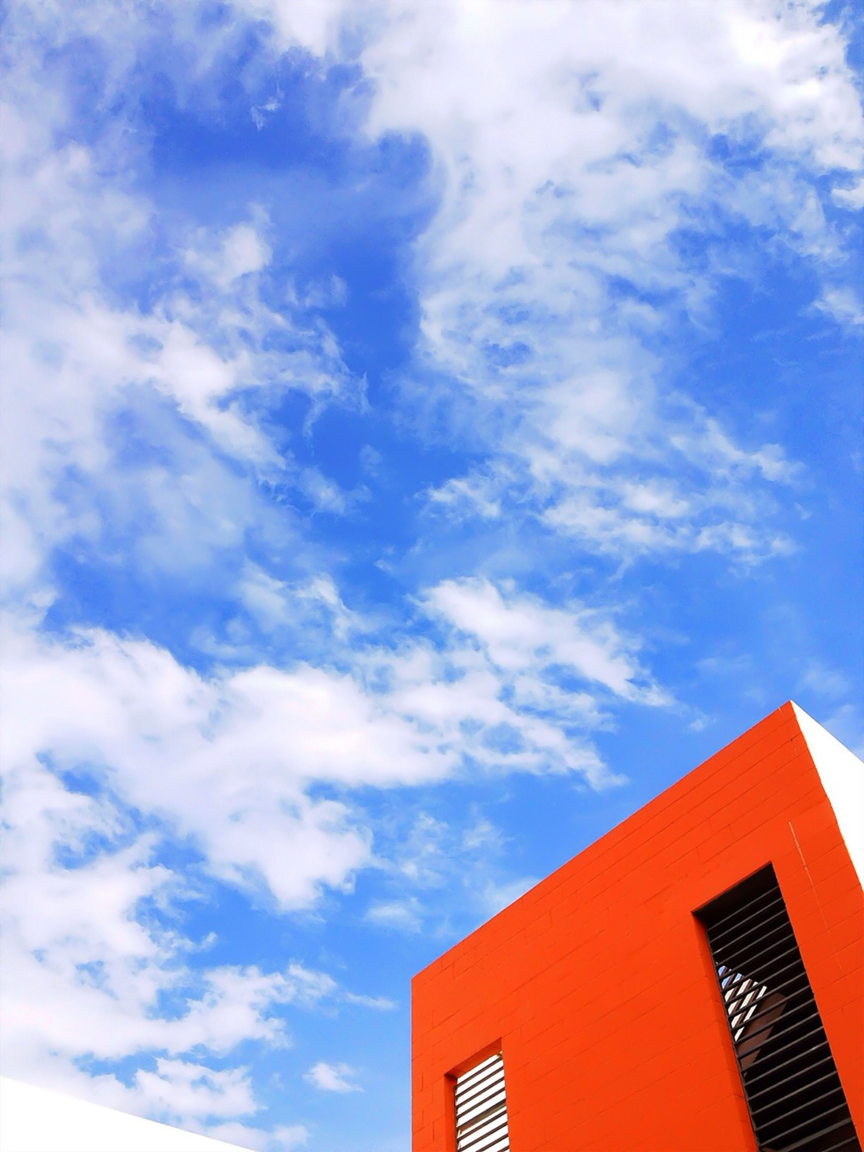 building exterior, architecture, low angle view, built structure, sky, cloud - sky, high section, cloud, residential structure, house, cloudy, residential building, blue, outdoors, building, window, day, no people, city, nature