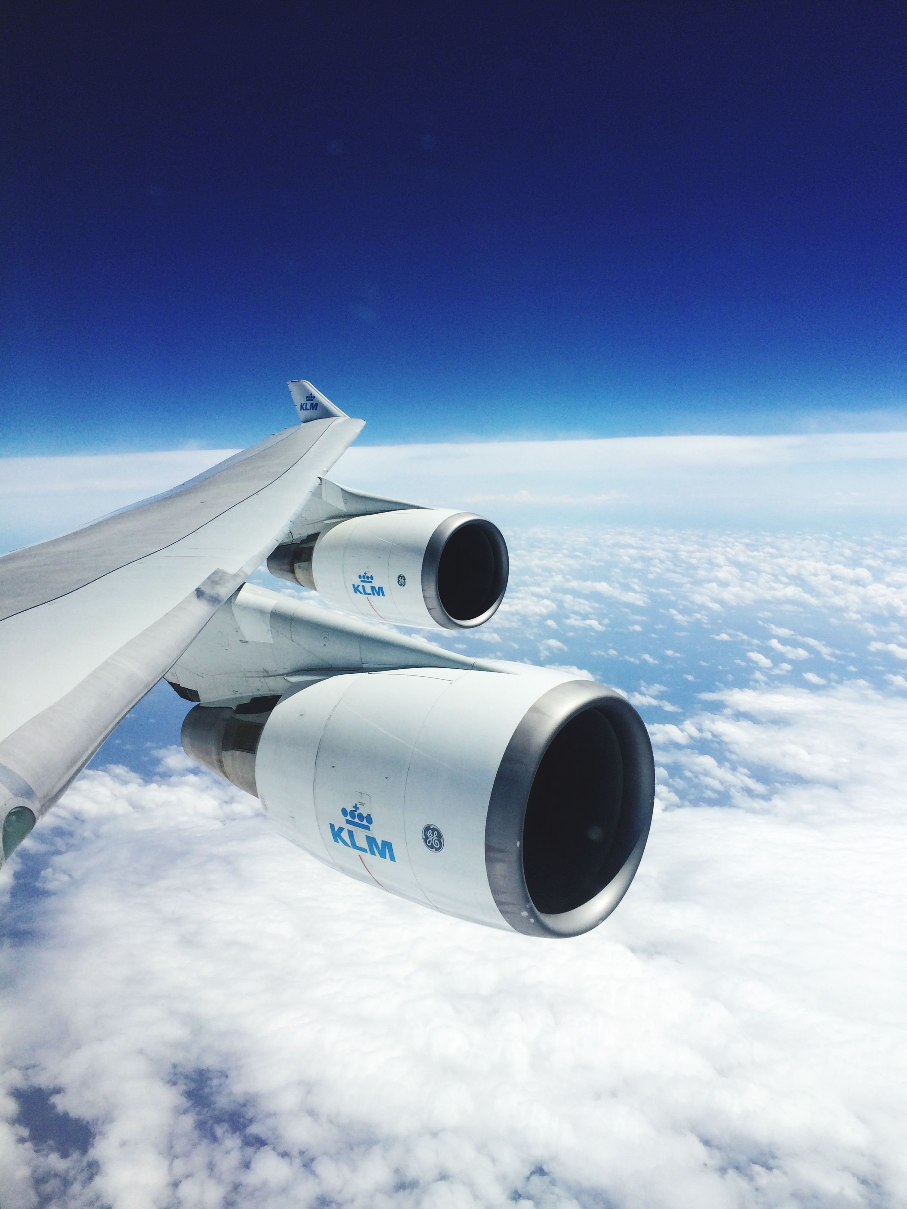 air vehicle, airplane, transportation, mode of transport, flying, aircraft wing, blue, sky, mid-air, journey, travel, part of, public transportation, cropped, cloud - sky, jet engine, aircraft, day, commercial airplane, white color