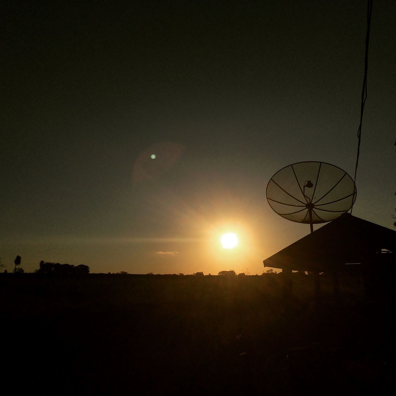 Silhouette Satellite Dish On Field During Sunset