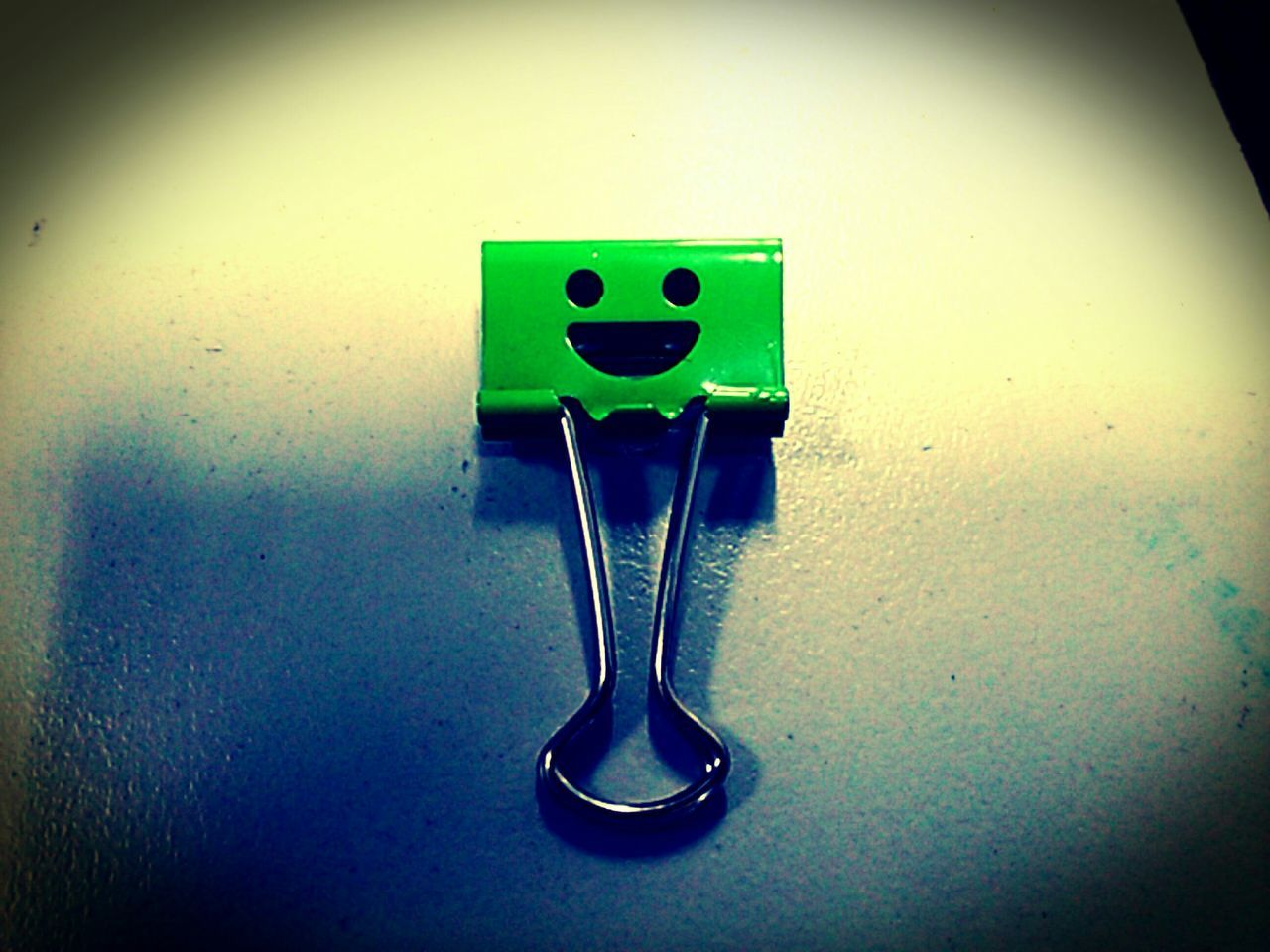 Close-Up Of Green Paper Clip On Table
