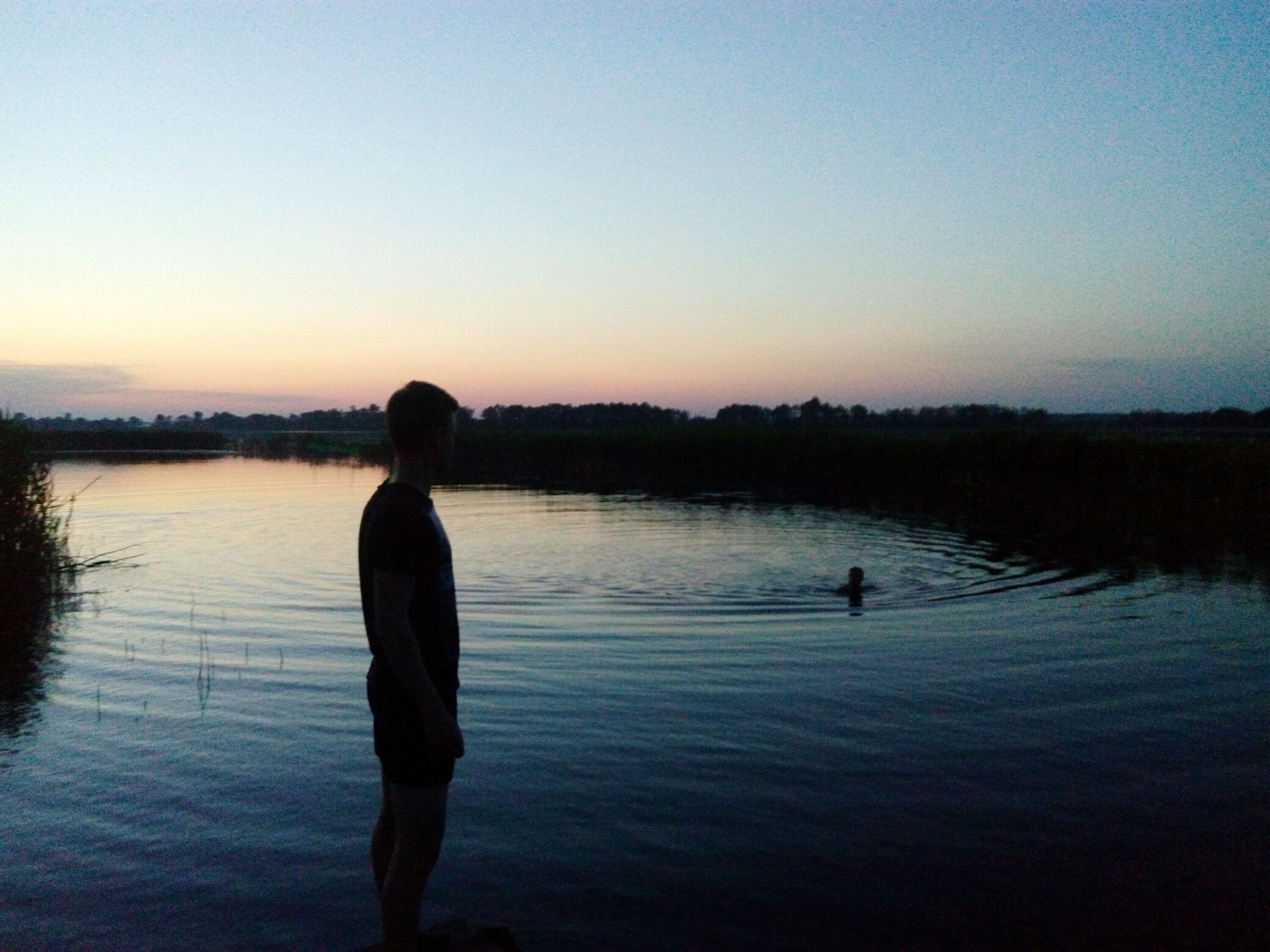 water, silhouette, lake, sunset, clear sky, tranquil scene, tranquility, reflection, scenics, copy space, men, standing, beauty in nature, nature, leisure activity, rear view, lifestyles, fishing