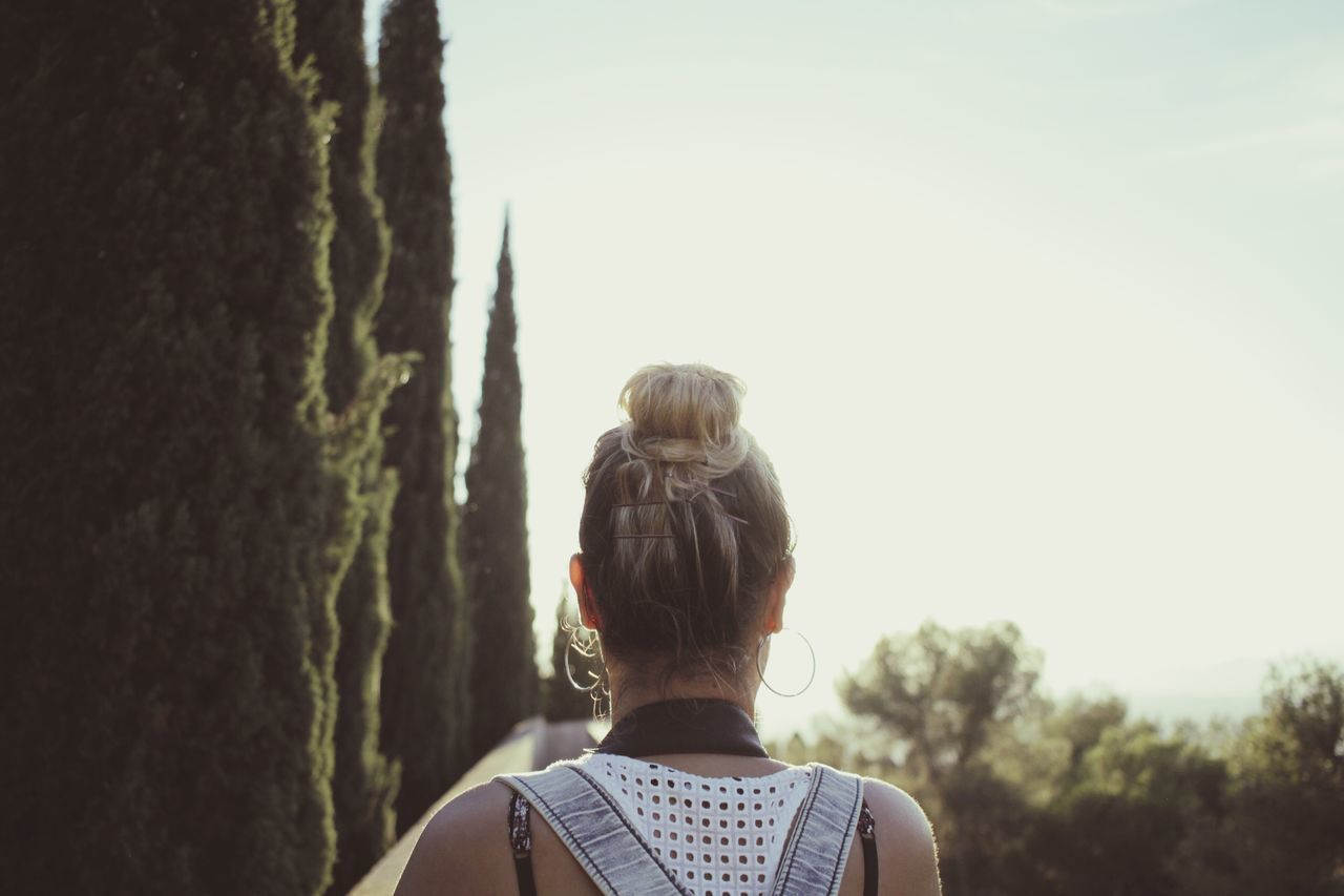 rear view, real people, hair bun, one person, women, leisure activity, clear sky, headshot, nature, day, outdoors, standing, lifestyles, sky, adventure, men, beauty in nature, people