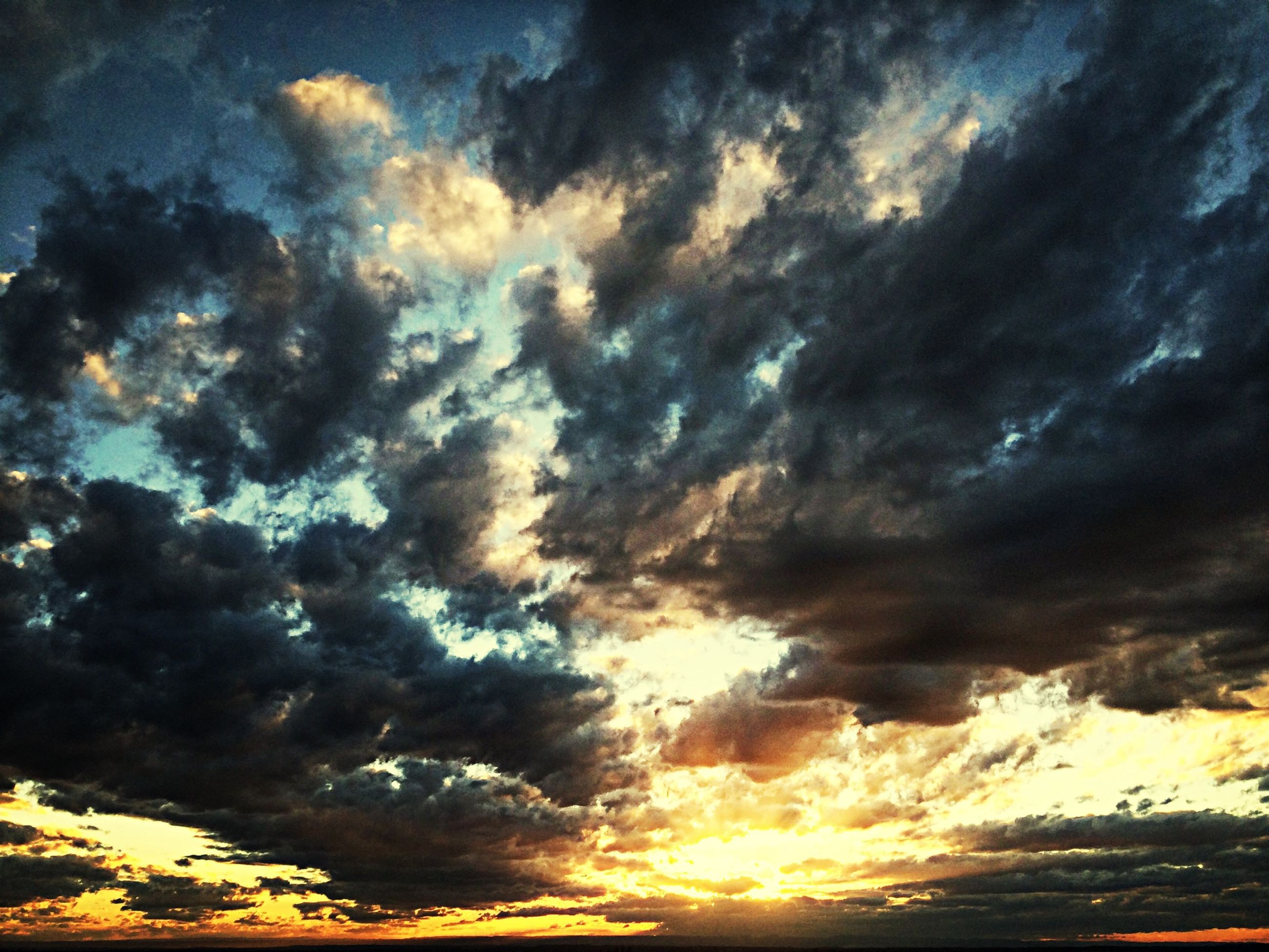 sky, cloud - sky, beauty in nature, scenics, sunset, tranquility, tranquil scene, cloudy, dramatic sky, nature, idyllic, orange color, low angle view, cloud, weather, cloudscape, overcast, majestic, atmospheric mood, moody sky
