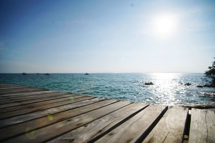 Investing In Quality Of Life Water Horizon Over Water Wood - Material Summer Outdoors Beauty In Nature Sunlight Scenics Vacations Sky Nature Sun Sunset Tranquil Scene Morning Sunrise EyeEmNewHere Path To The Beach Wooden Structure Wooden Bridge Wooden Floor Vacations 3layers Layered Photos