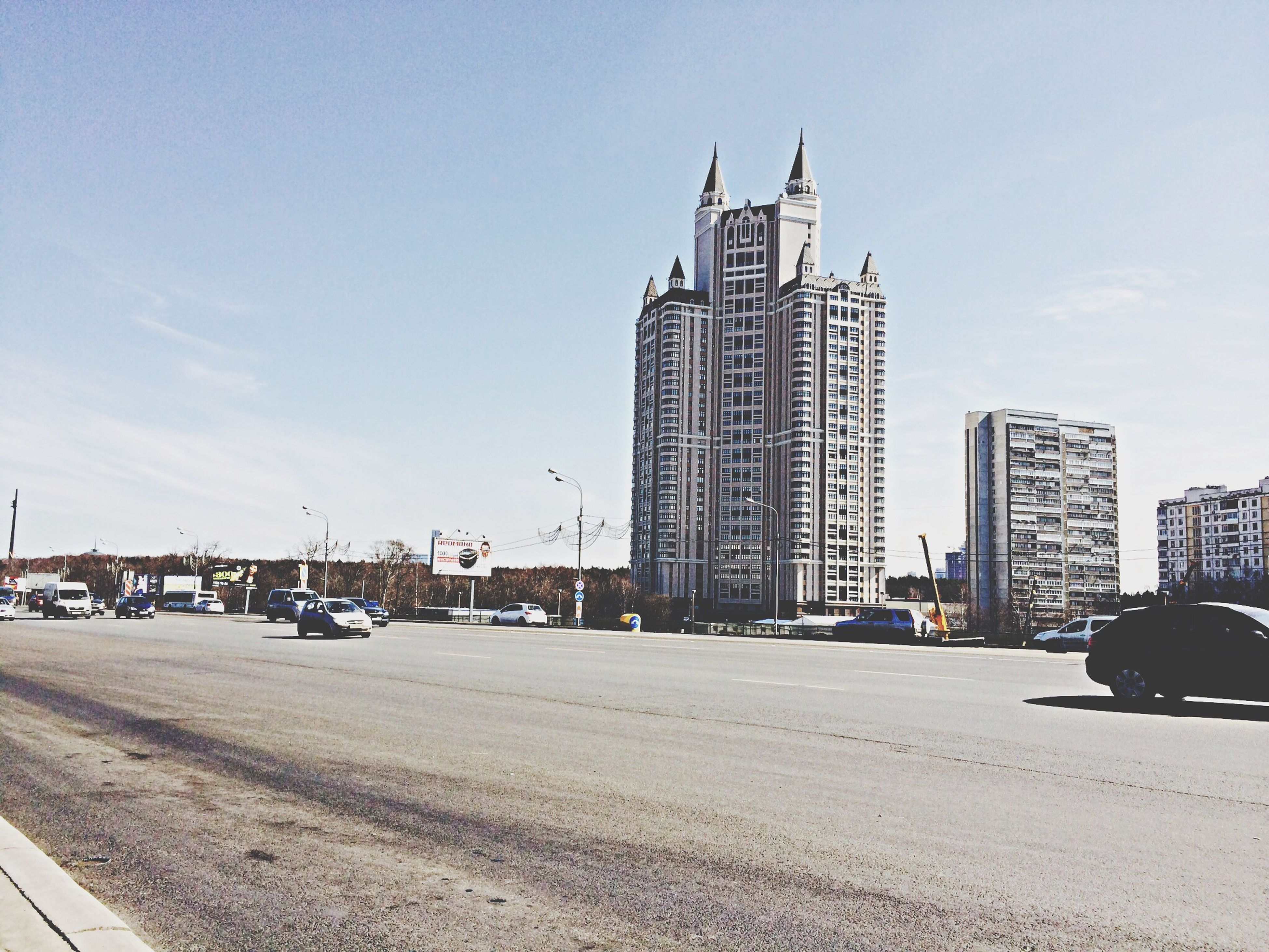 building exterior, architecture, built structure, city, transportation, clear sky, street, road, tower, sky, car, mode of transport, copy space, skyscraper, land vehicle, day, tall - high, incidental people, building, blue