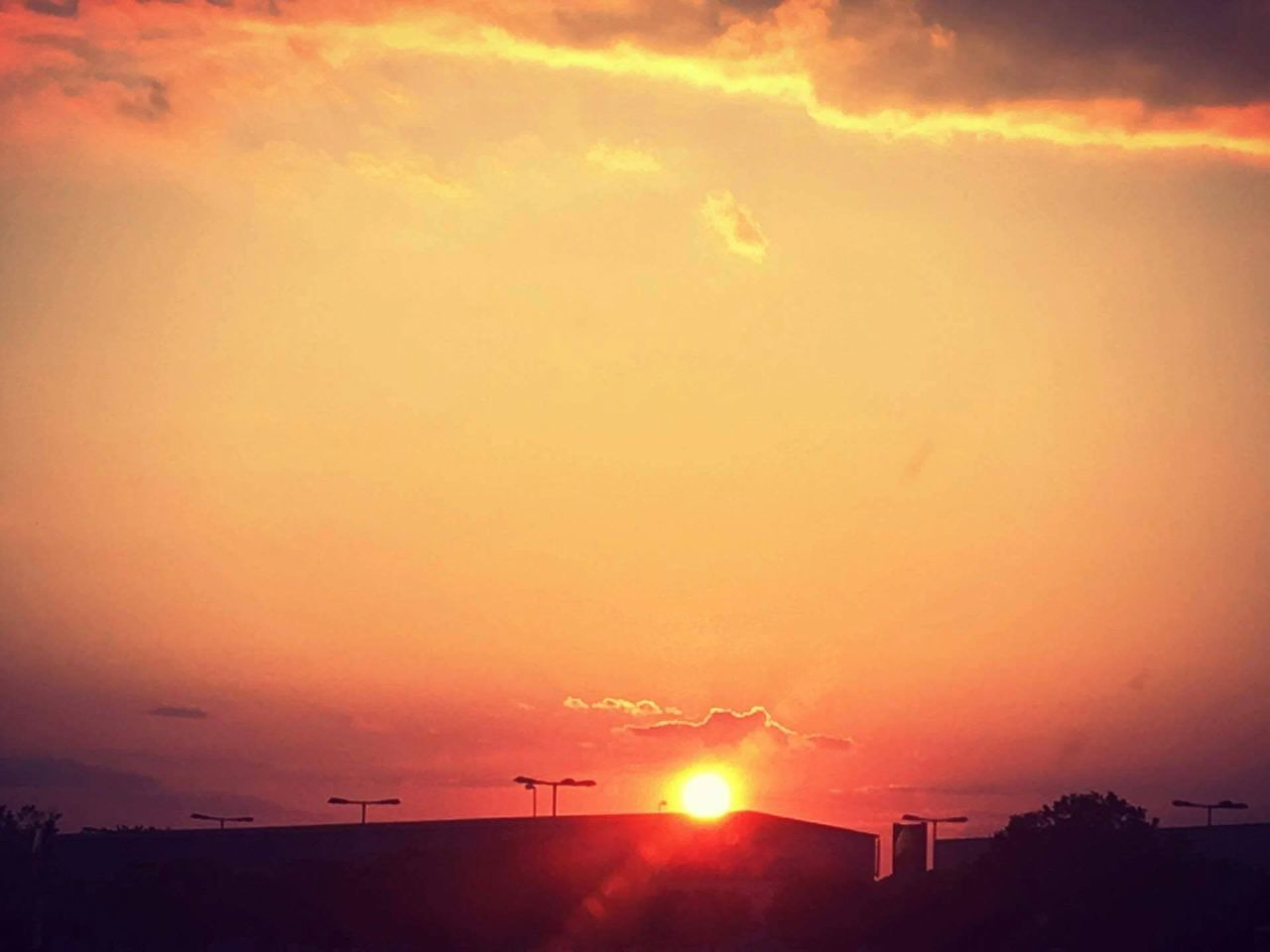 sunset, sun, orange color, sky, silhouette, beauty in nature, nature, dramatic sky, scenics, sunbeam, cloud - sky, outdoors, no people, tranquility, tranquil scene, built structure, building exterior, architecture, day