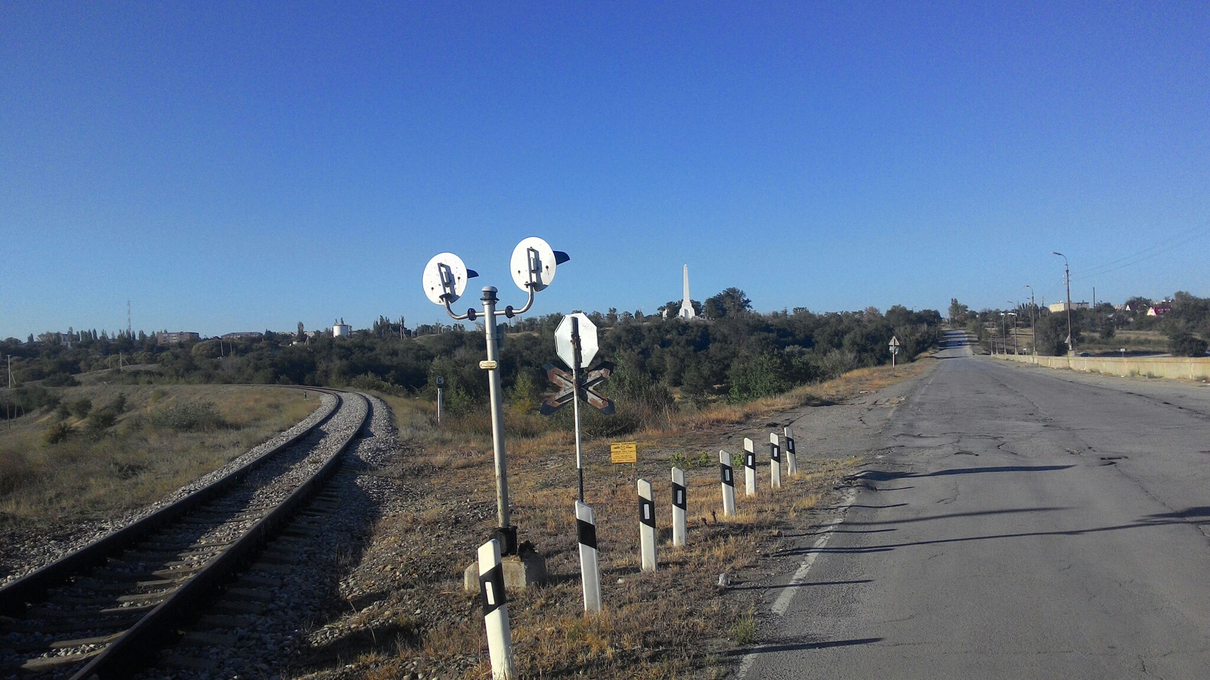 clear sky, the way forward, copy space, blue, transportation, road, diminishing perspective, vanishing point, landscape, sky, in a row, empty, field, day, long, outdoors, railroad track, street, country road, road marking