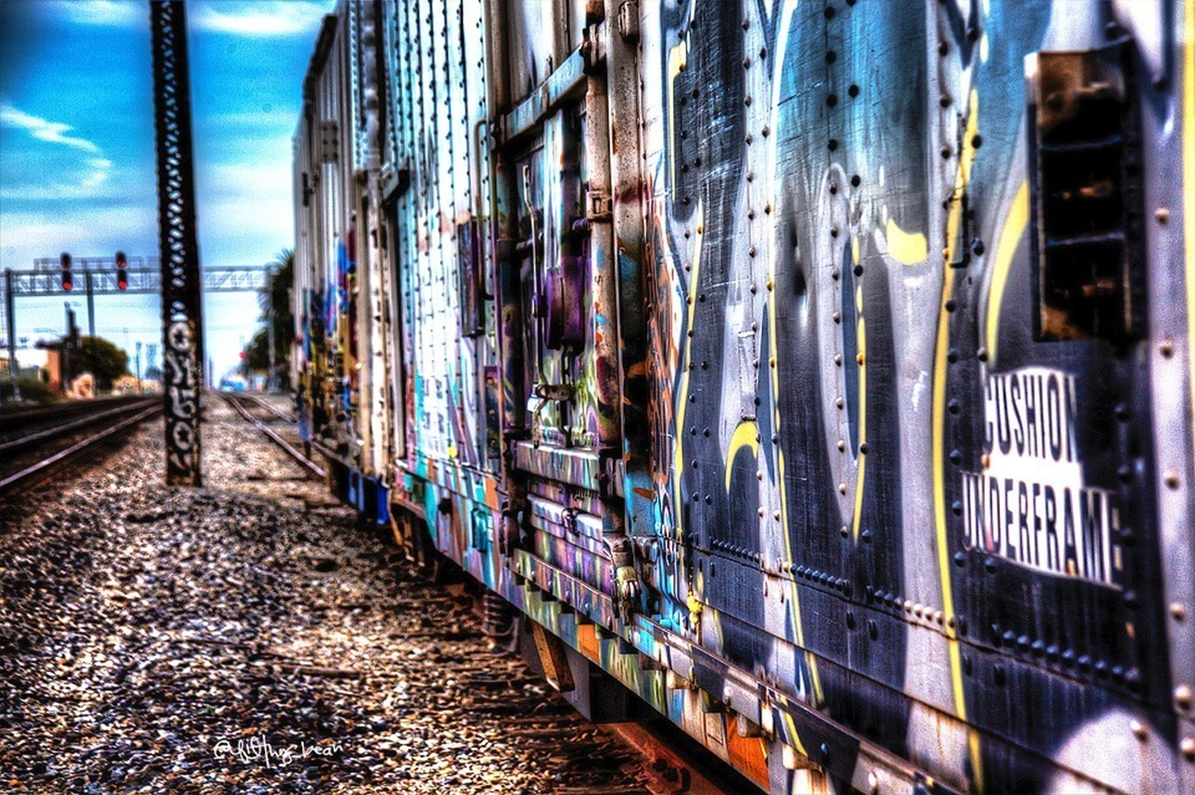 architecture, built structure, building exterior, transportation, city, graffiti, railroad track, public transportation, building, incidental people, rail transportation, glass - material, day, mode of transport, reflection, city life, railroad station platform, street, outdoors, diminishing perspective