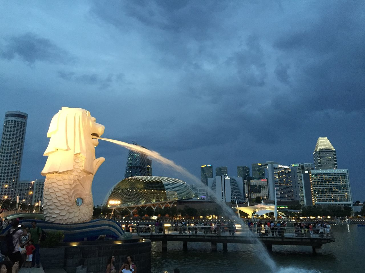 Water Coming Out From Merlion Statue Against Buildings And Sky At Park