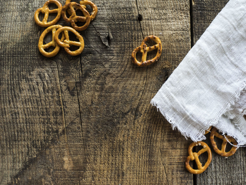Heap of fresh Wheat salt pretzels on hessian linen fabric cloth and wooden table Cloth Creativity Fabric Fresh Geometric Shape Heap Hessian High Angle View Linen Man Made Object No People Pretzels Salt Symbol Table Wheat Wooden