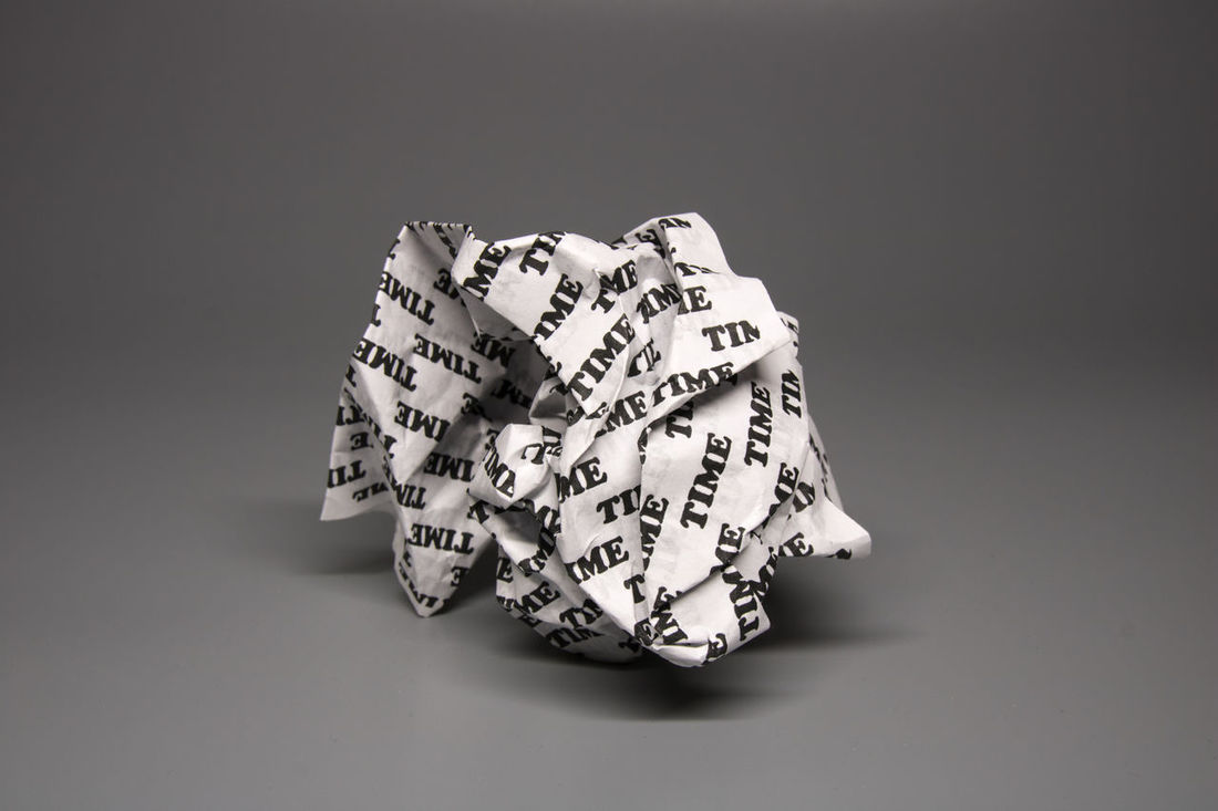 """A crumpled paper with the word """"time"""" written all over it on a grey background. This concept is about time being wasted like a crumpled piece of paper. Looking almost black and white it reflects a sad feeling of time lost. The idea of time about to be thrown away to the garbage, or the past being destroyed. Buisness Bureacracy Concept Crumpled Death Error Freelancer Goals Grey Impractical Management Melancholic Mistakes  Paper Procrastination Social Media Uneconomical Unfair Unfortunate Use Useless Valuable Wasted Youth"""