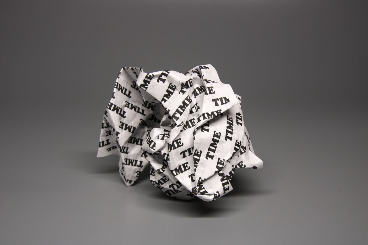 "A crumpled paper with the word ""time"" written all over it on a grey background. This concept is about time being wasted like a crumpled piece of paper. Looking almost black and white it reflects a sad feeling of time lost. The idea of time about to be thrown away to the garbage, or the past being destroyed. Buisness Bureacracy Concept Crumpled Death Error Freelancer Goals Grey Impractical Management Melancholic Mistakes  Paper Procrastination Social Media Uneconomical Unfair Unfortunate Use Useless Valuable Wasted Youth"