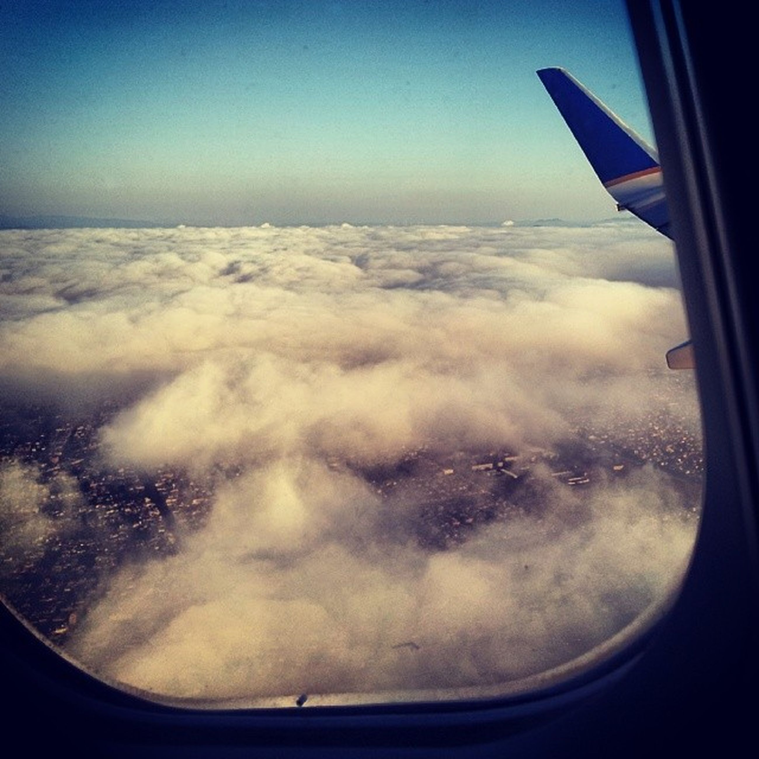 transportation, mode of transport, airplane, air vehicle, vehicle interior, window, aircraft wing, flying, part of, glass - material, transparent, travel, cropped, on the move, aerial view, journey, sky, vehicle part, mid-air, landscape