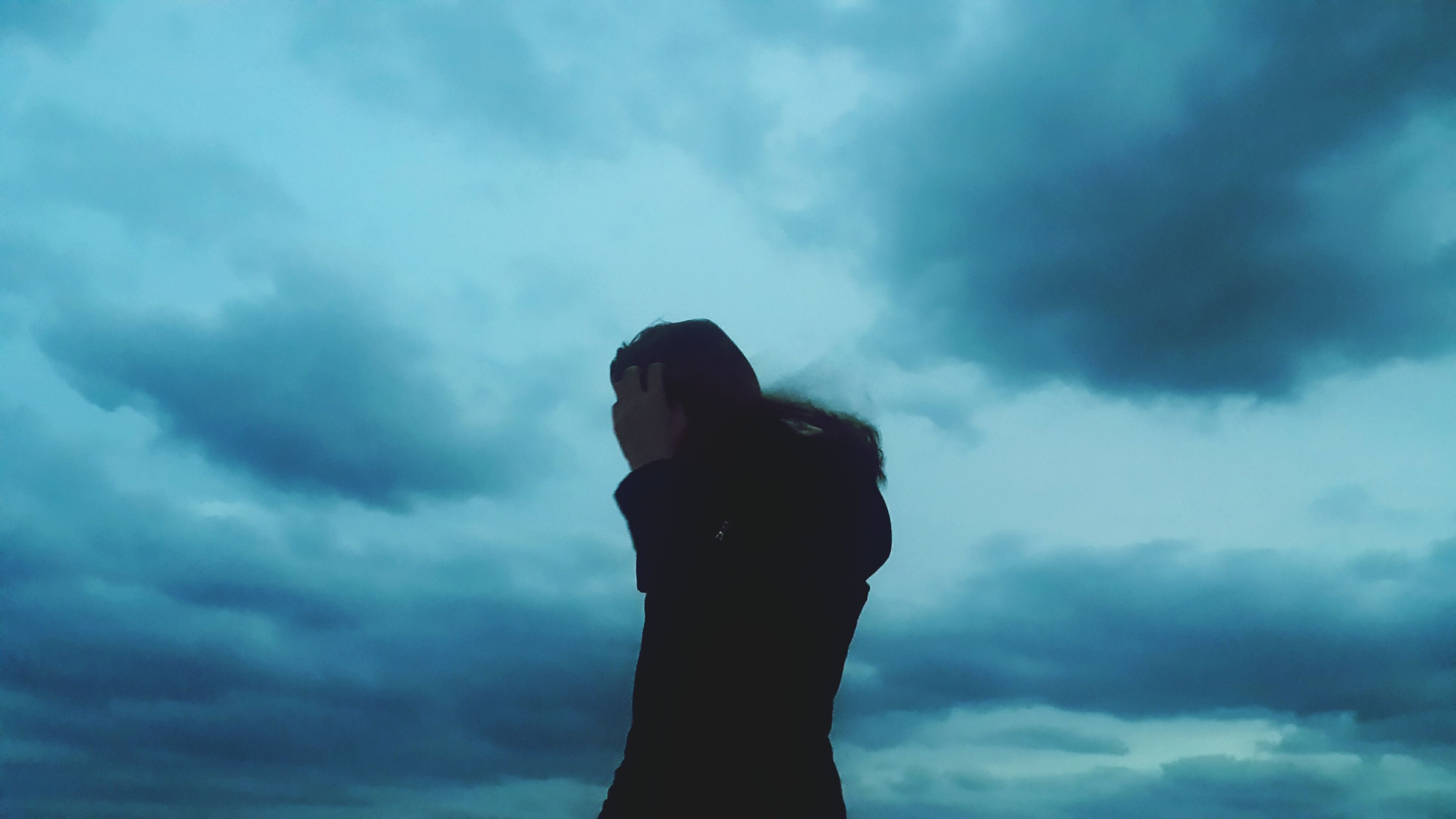 three quarter length, sky, standing, silhouette, cloud - sky, low angle view, leisure activity, waist up, lifestyles, cloudy, person, blue, carefree, cloud, outdoors, atmospheric mood, outline