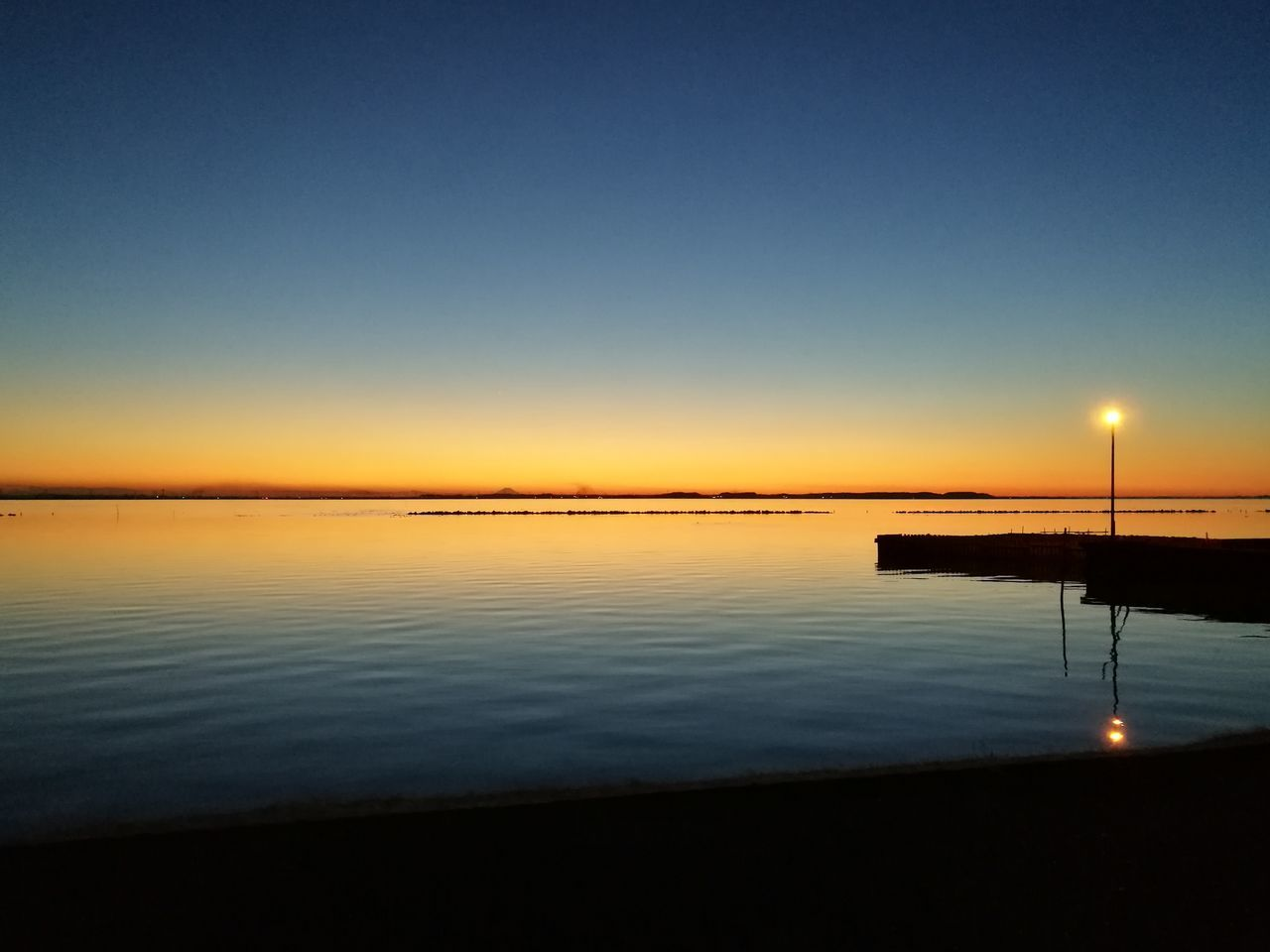 sunset, tranquil scene, scenics, beauty in nature, tranquility, water, nature, idyllic, sky, silhouette, no people, reflection, outdoors, sea, blue, clear sky, night