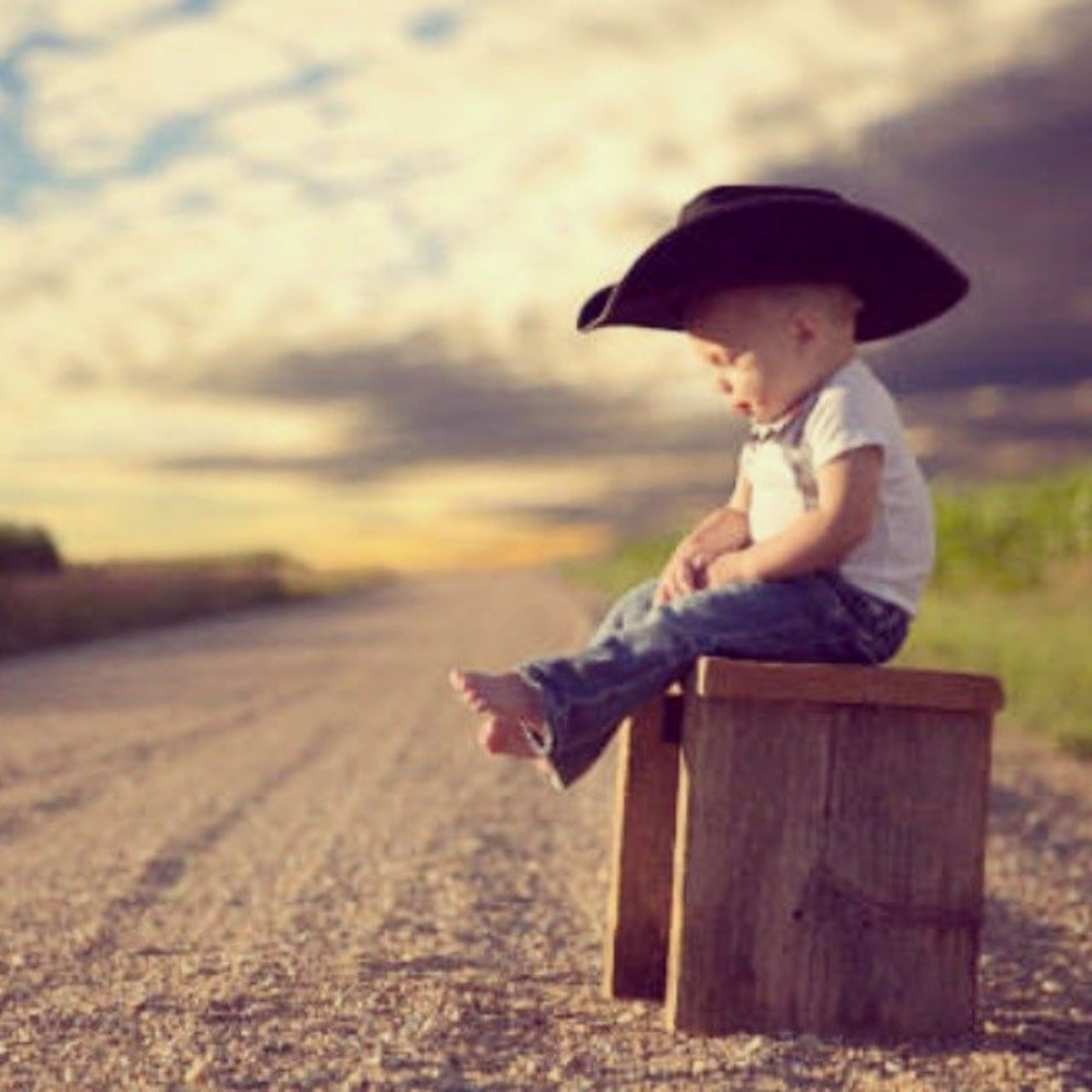 focus on foreground, full length, side view, outdoors, lifestyles, childhood, field, holding, day, leisure activity, rear view, sitting, casual clothing, toy, selective focus, hat, sunlight, nature