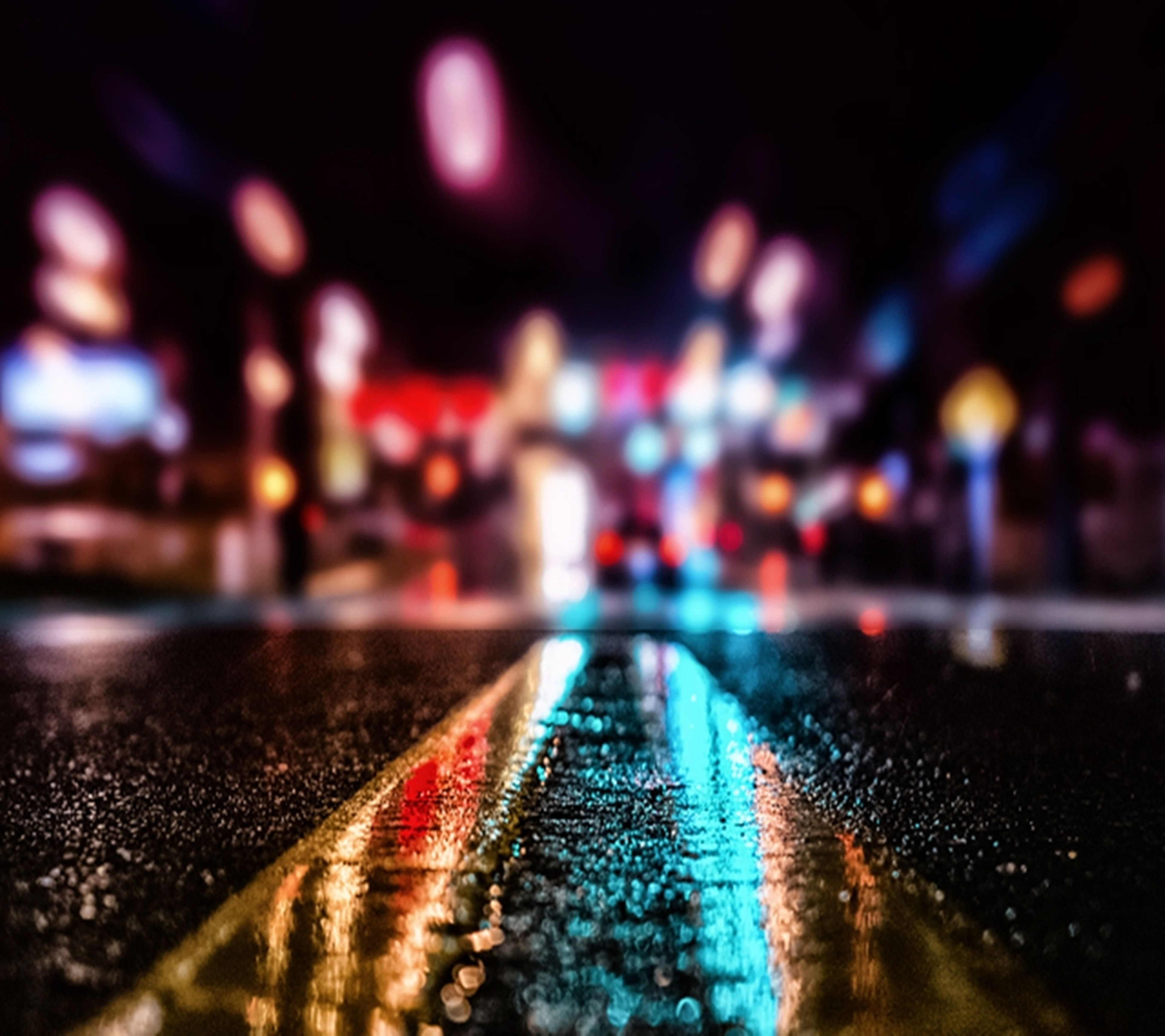 surface level, selective focus, the way forward, illuminated, night, diminishing perspective, street, focus on foreground, vanishing point, defocused, road, outdoors, cobblestone, close-up, no people, transportation, footpath, built structure, pattern, empty