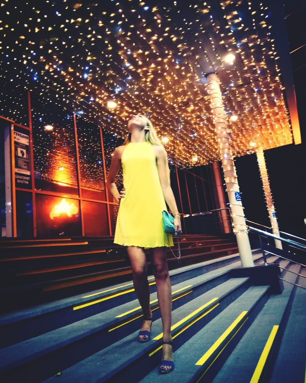 full length, illuminated, night, real people, rear view, one person, lifestyles, standing, built structure, leisure activity, yellow, outdoors, young adult, building exterior, architecture, city, women, young women, sky, adult, people