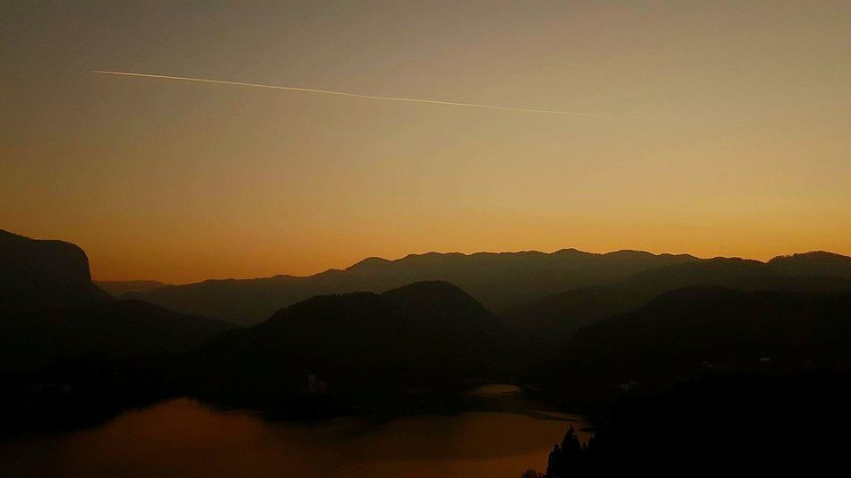 Slovenian sunset 😍 Sunset Reflection Silhouette Landscape Fog Mountain Sun Nature Outdoors Beauty In Nature Travel Destinations Beauty Sky Scenics Tranquility Arrival No People Tree Dawn Multi Colored Slovenia Bled, Slovenia Lakebled Sunset Silhouettes