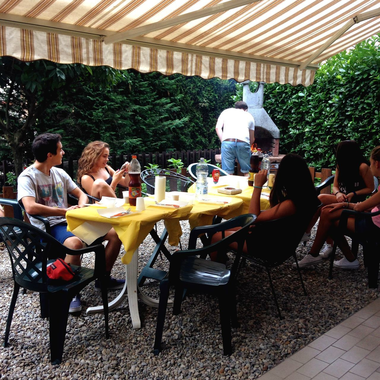 sitting, restaurant, real people, food and drink, togetherness, chair, table, men, casual clothing, full length, leisure activity, day, tree, lifestyles, cafe, outdoors, women, relaxation, friendship, food, eating, drink, large group of people, young adult, young women, people
