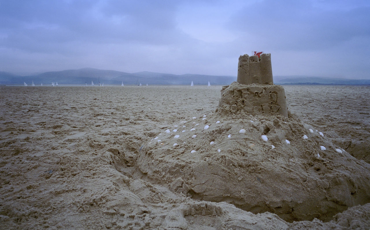 grainy: sandcastle at an wales beach Castle Childrens Play Thing Construction Flag Fortification Fortify Moat Sand Scenics Sea Shell Sky Tower Uk Wales Yachts