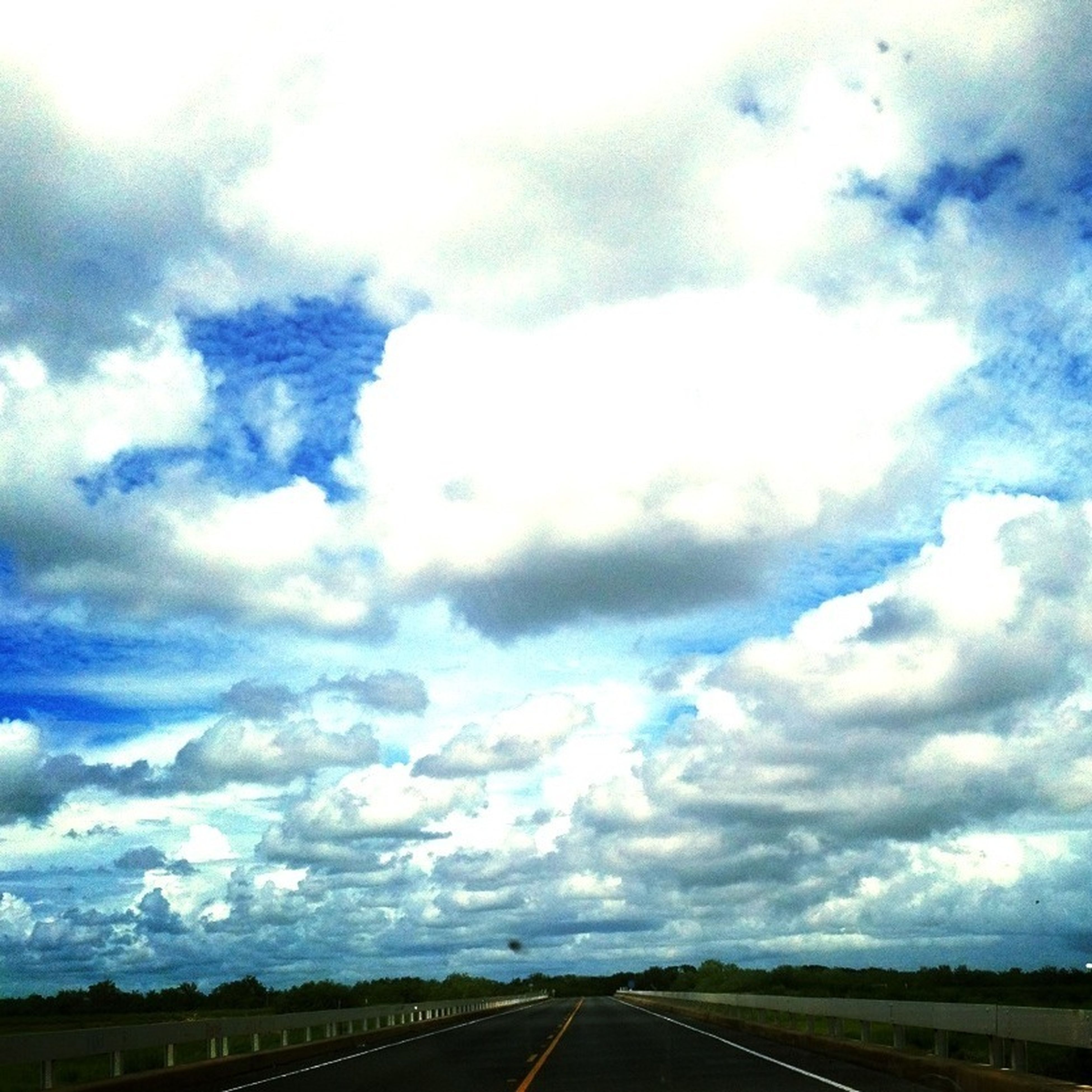 sky, transportation, the way forward, cloud - sky, road, diminishing perspective, cloudy, vanishing point, cloud, road marking, tranquil scene, tranquility, landscape, nature, scenics, overcast, beauty in nature, weather, cloudscape, outdoors