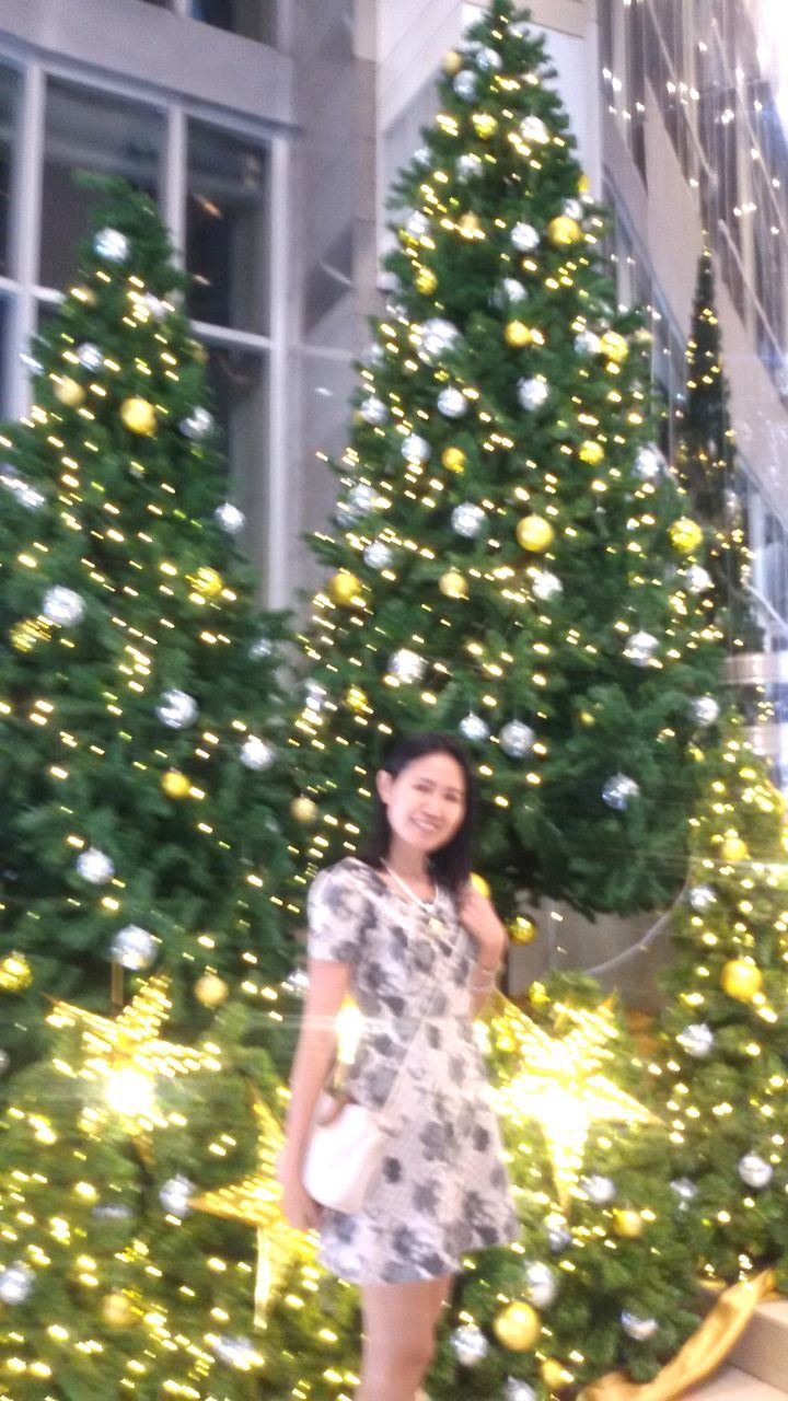 smiling, tree, happiness, one person, young adult, blurred motion, real people, christmas lights, lifestyles, night, motion, christmas, low angle view, outdoors, young women, christmas decoration, cheerful, illuminated, portrait, architecture, people