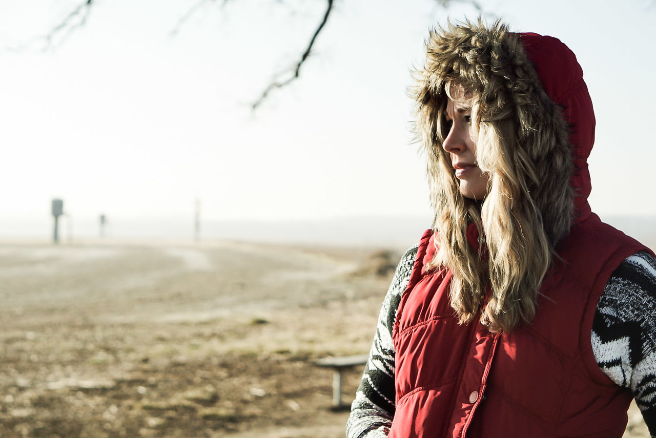 Close-Up Of Young Woman Wearing Hood Standing On Field During Winter