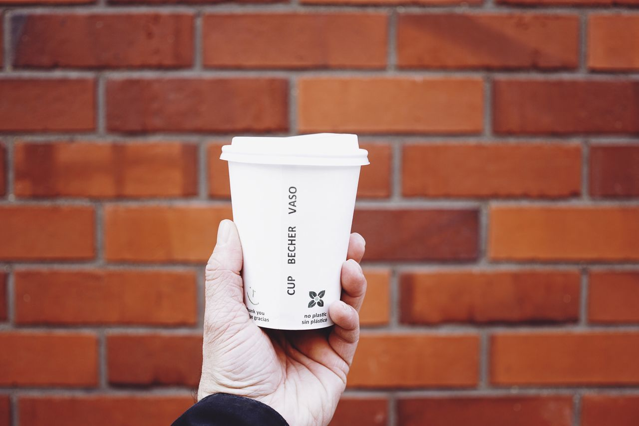 Holding a cup of coffee cup paper to go hand holding white Red Brick Wall Man male Beverage Hot 8ung hamburg