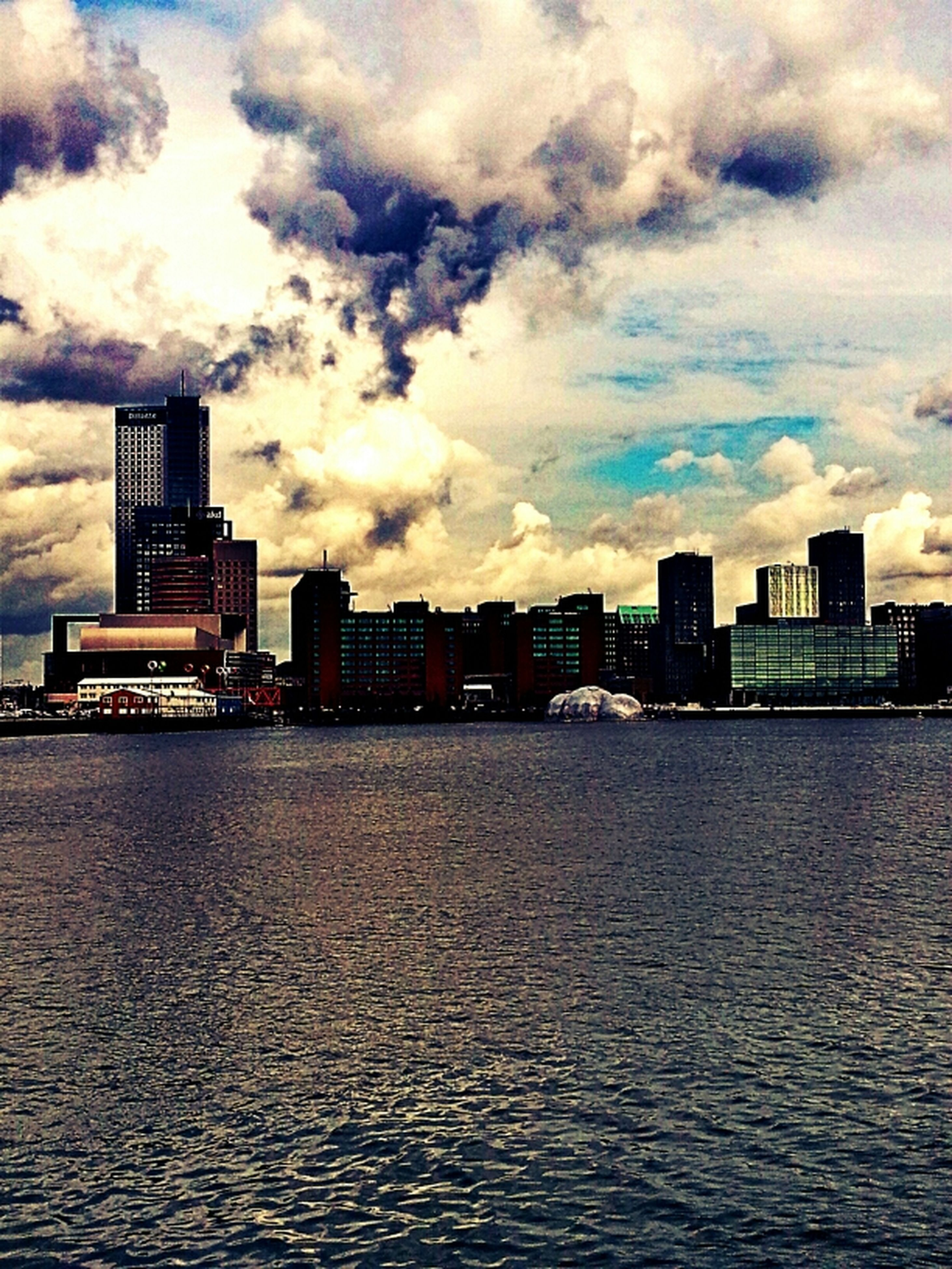building exterior, architecture, built structure, sky, waterfront, cloud - sky, cloudy, water, city, cloud, sunset, rippled, building, weather, overcast, river, residential building, sea, dusk, residential structure