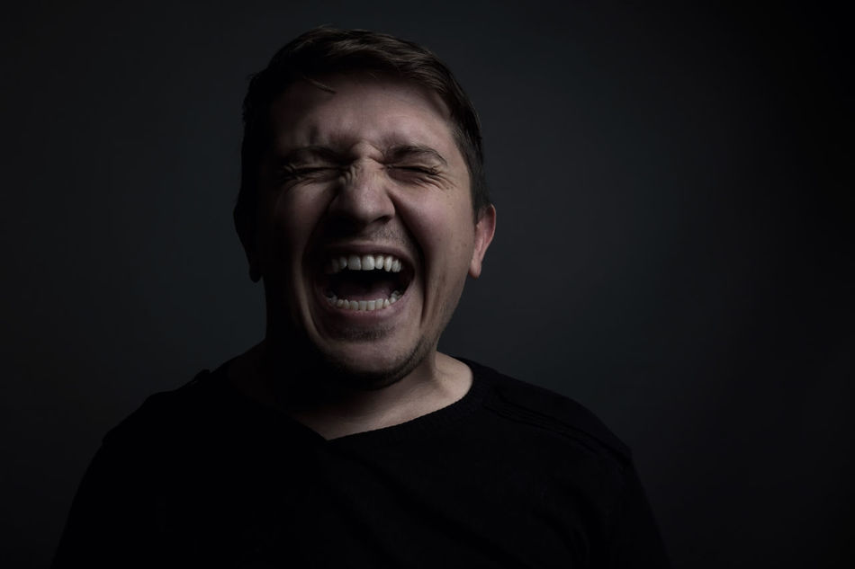 portrait of man yell of pain in front of grey background Feeling Man Pain Stress Anger Black Background Emotion Eyes Closed  Facial Expression Front View Frustration Headshot Male Mouth Open One Person Painful Pissed Portrait Screaming Screaming_shots Shouting Studio Shot Yelling