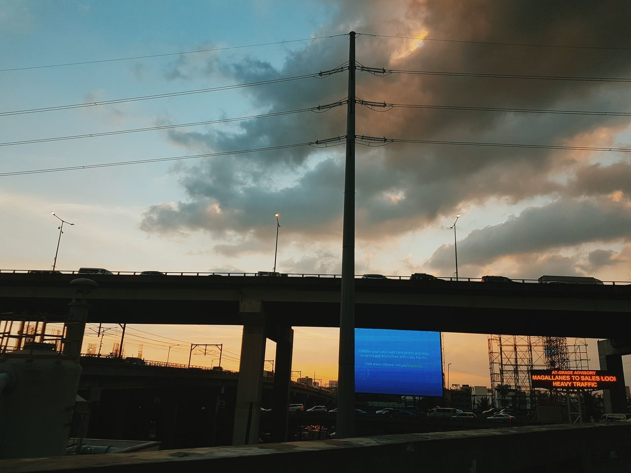 sky, cloud - sky, built structure, architecture, building exterior, connection, transportation, sunset, outdoors, cable, no people, electricity pylon, land vehicle, day, city, nature, tree