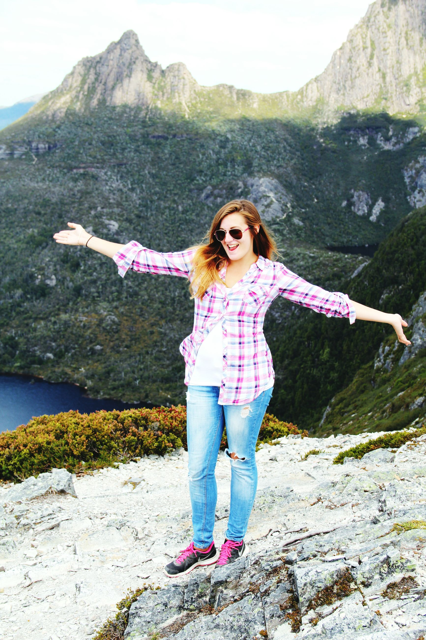 casual clothing, lifestyles, mountain, person, leisure activity, standing, full length, young adult, looking at camera, portrait, smiling, young women, front view, water, mountain range, three quarter length, happiness, nature