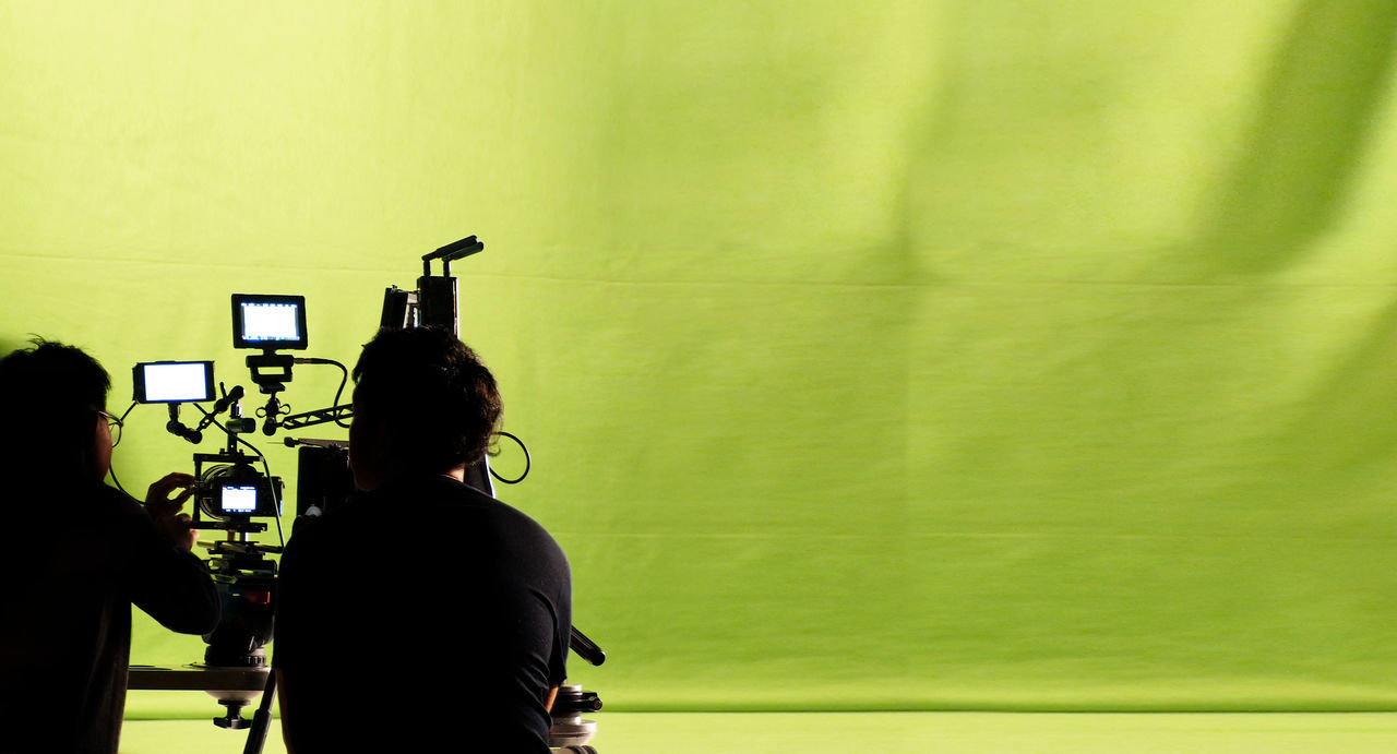 Behind the video production camera set and crew team shooting in a big green screen studio. Camera Day Green Screen Indoors  Men People Photography Themes Real People Studio Studio; Video; Camera; Television; Film; Tv; Green; Screen; Equipment; Set; Photography; Production; Movie; Media; Professional; Technology; Tripod; Broadcast; Light; Photographer; Background; Broadcasting; News; Stage; Work; Photographic; Industry; Crew; Technology Two People